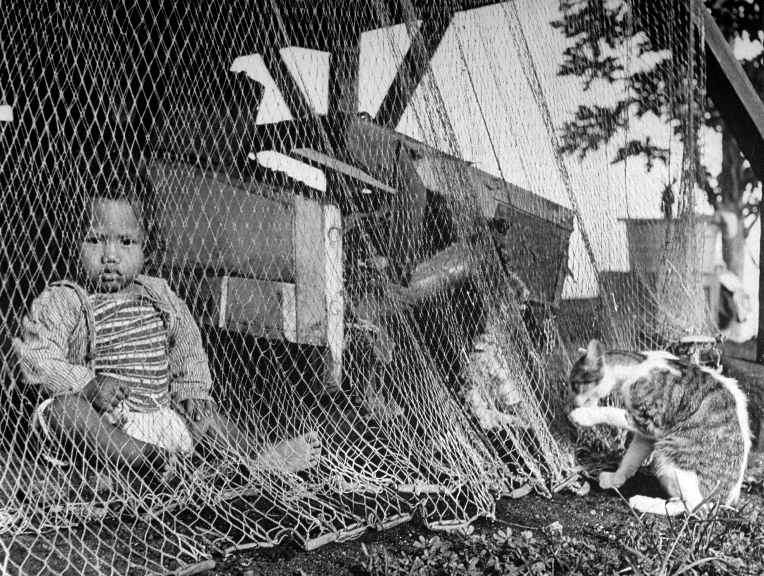 A fishing net hangs out to dry in front of a fisherman's house, while a young child sits underneath.