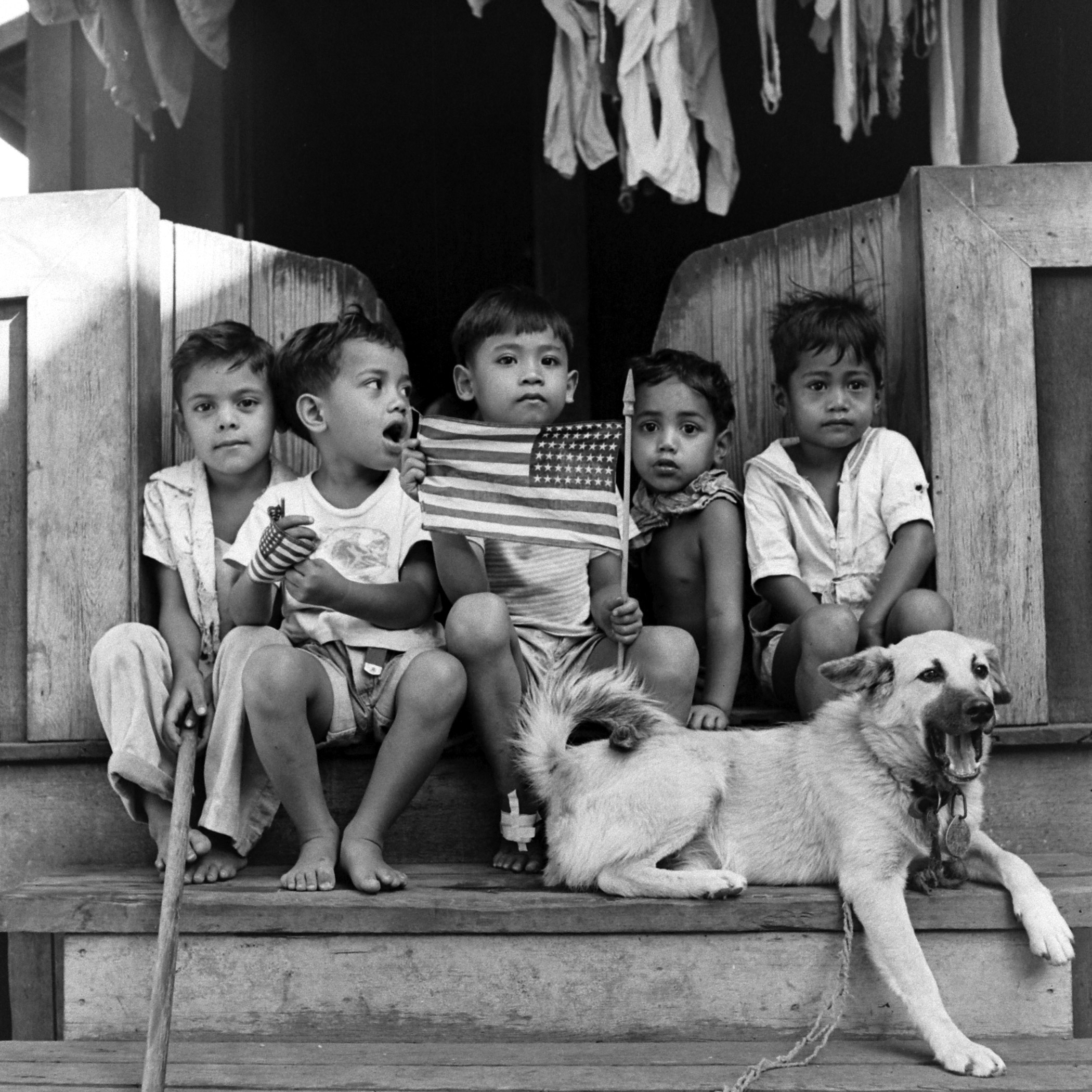 Children with an American flag hang out on a front porch.