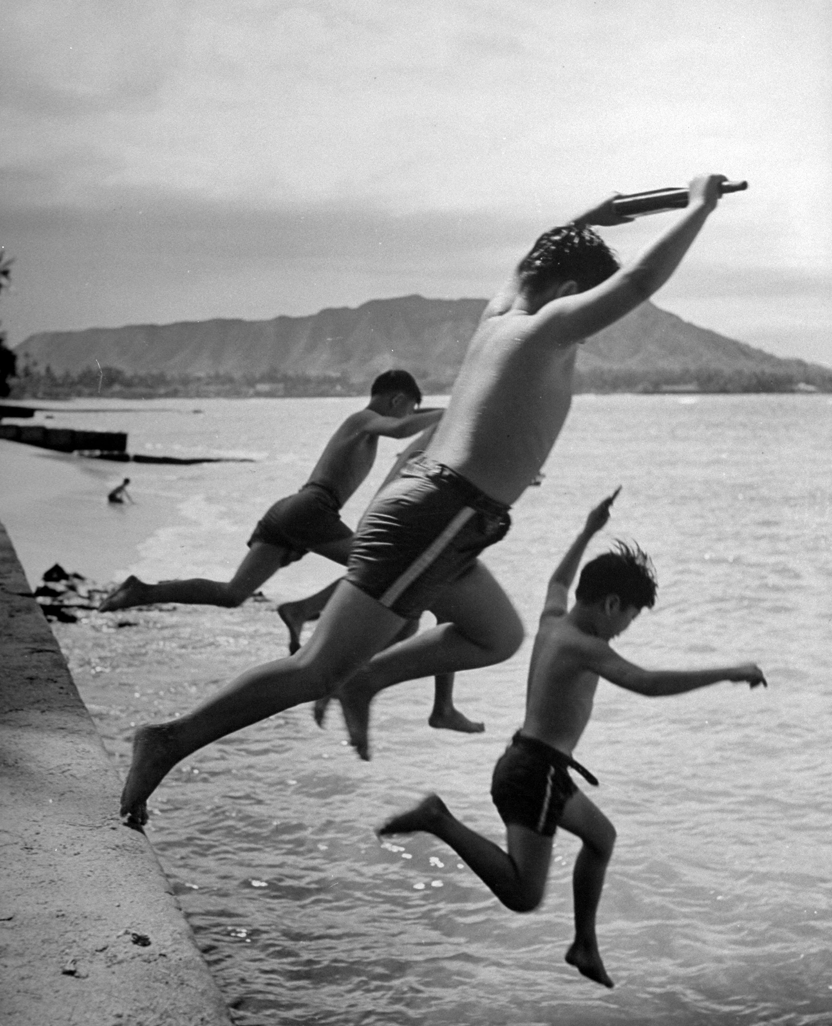 Japanese boys jump from a sea wall while playing soldiers in the American army.