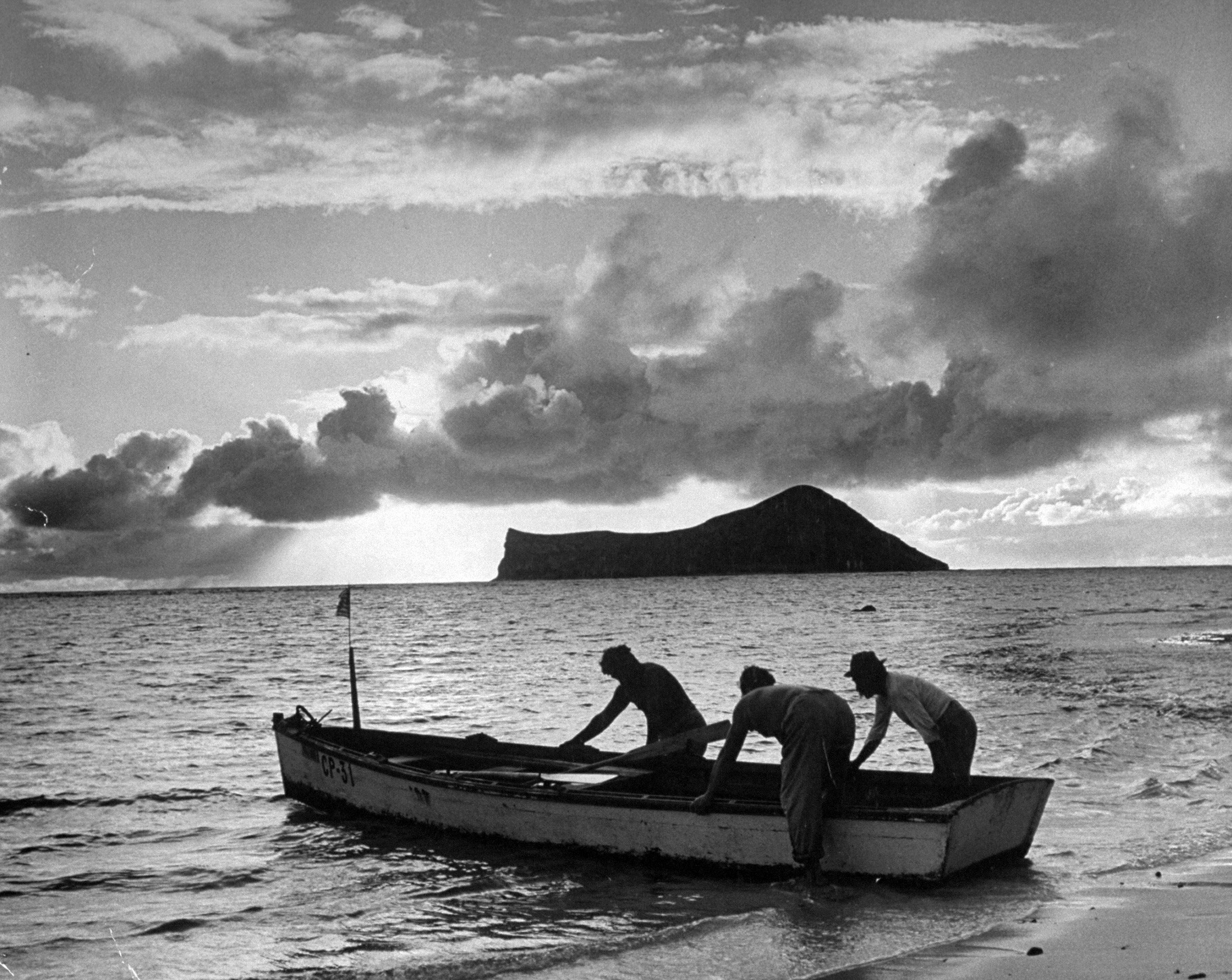 <b>Caption from LIFE.</b> At dawn Hawaiians put out to sea to pull in their fish nets. By law, their boat flies the American flag at bow.