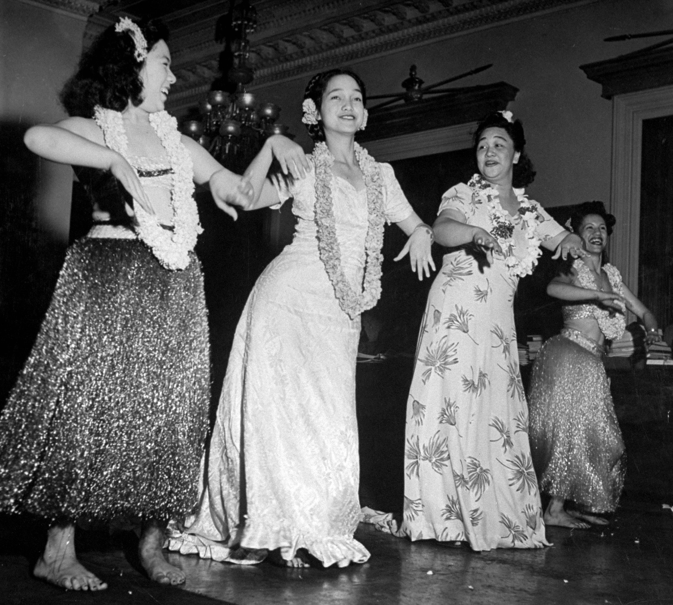 Women dressed in hula skirts dance onstage.