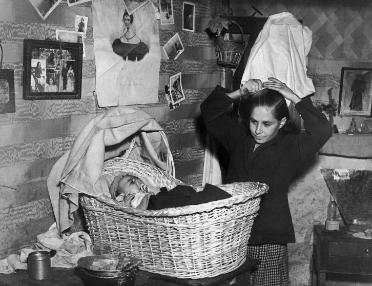 Young mother and her child in their shack-like residence set up in a cellar in Margellina, Naples in 1947.