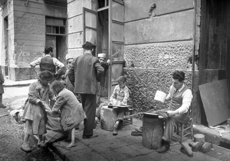 Kids in slum neighborhood helping prepare cardboard for shoe soles of recycled shoes that will be sold as new. Naples, Italy, 1947.