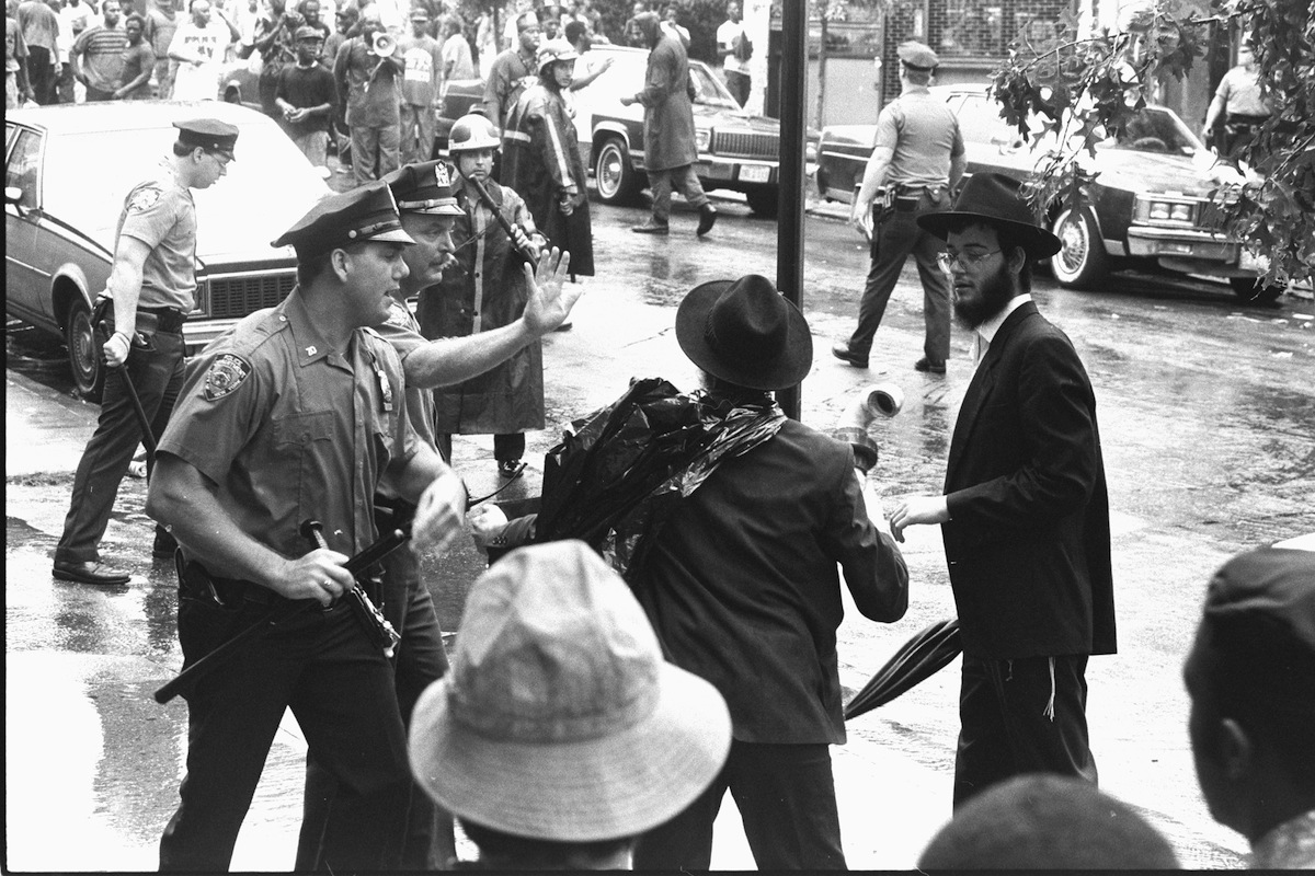 Police officers try to calm Hasidim during a confrontation at Utica Ave. and President St. during Crown Heights riots in August of 1991.