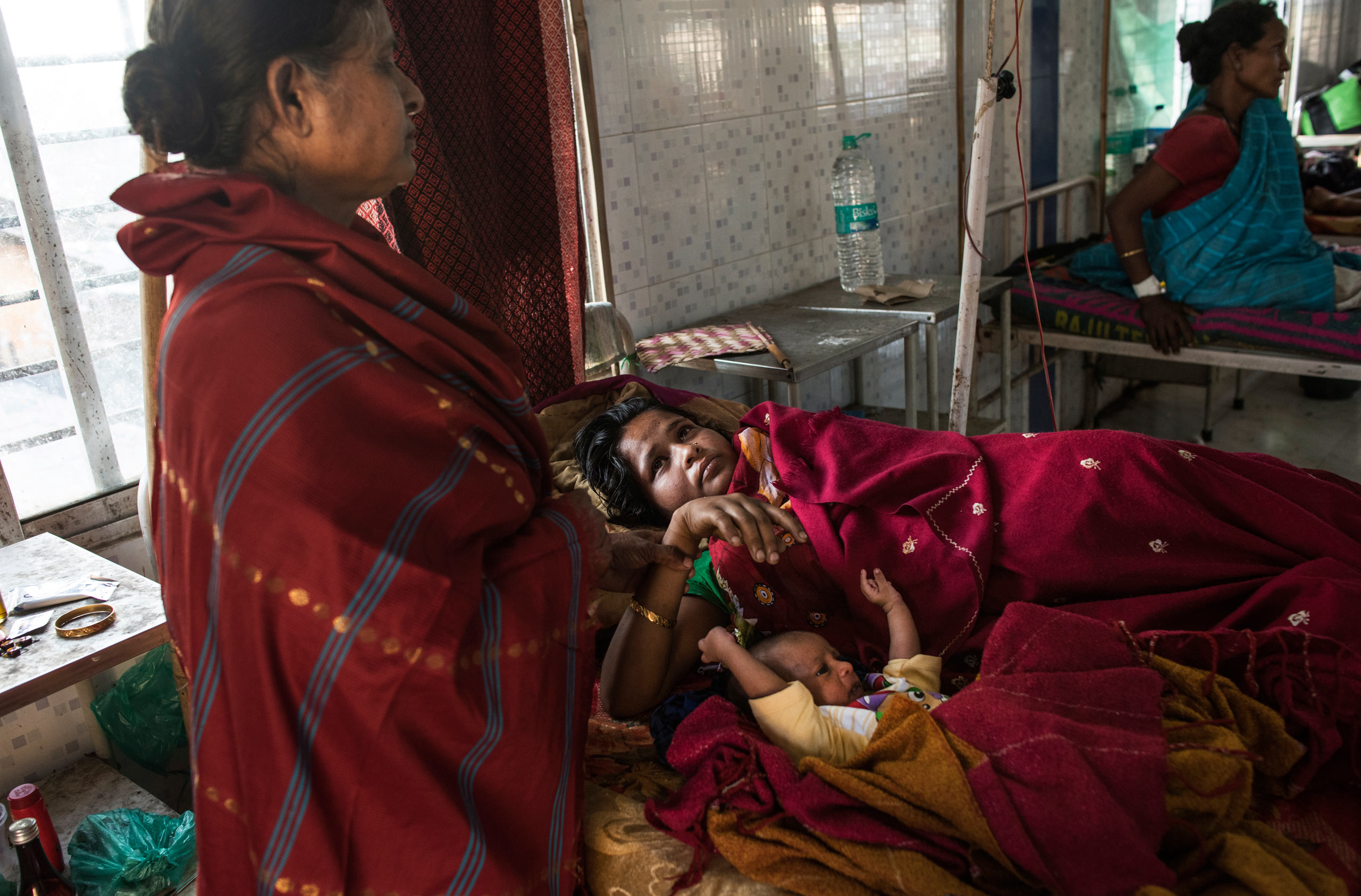 Nazreen Khatoon is comforted by her mother as she lies gravely ill, suffering from severe postpartum anemia, at the Tezpur Civil Hospital in Tezpur, Assam, India. April 2015. Khatoon delivered her son, Kashari Pam, three weeks prior, and returned to the hospital two weeks after delivery when her condition worsened. In dire need of both blood and iron, she was not receiving either from the Tezpur Hospital. She was eventually referred to a private hospital, where she was able to receive better care, but at a great expense to the family.