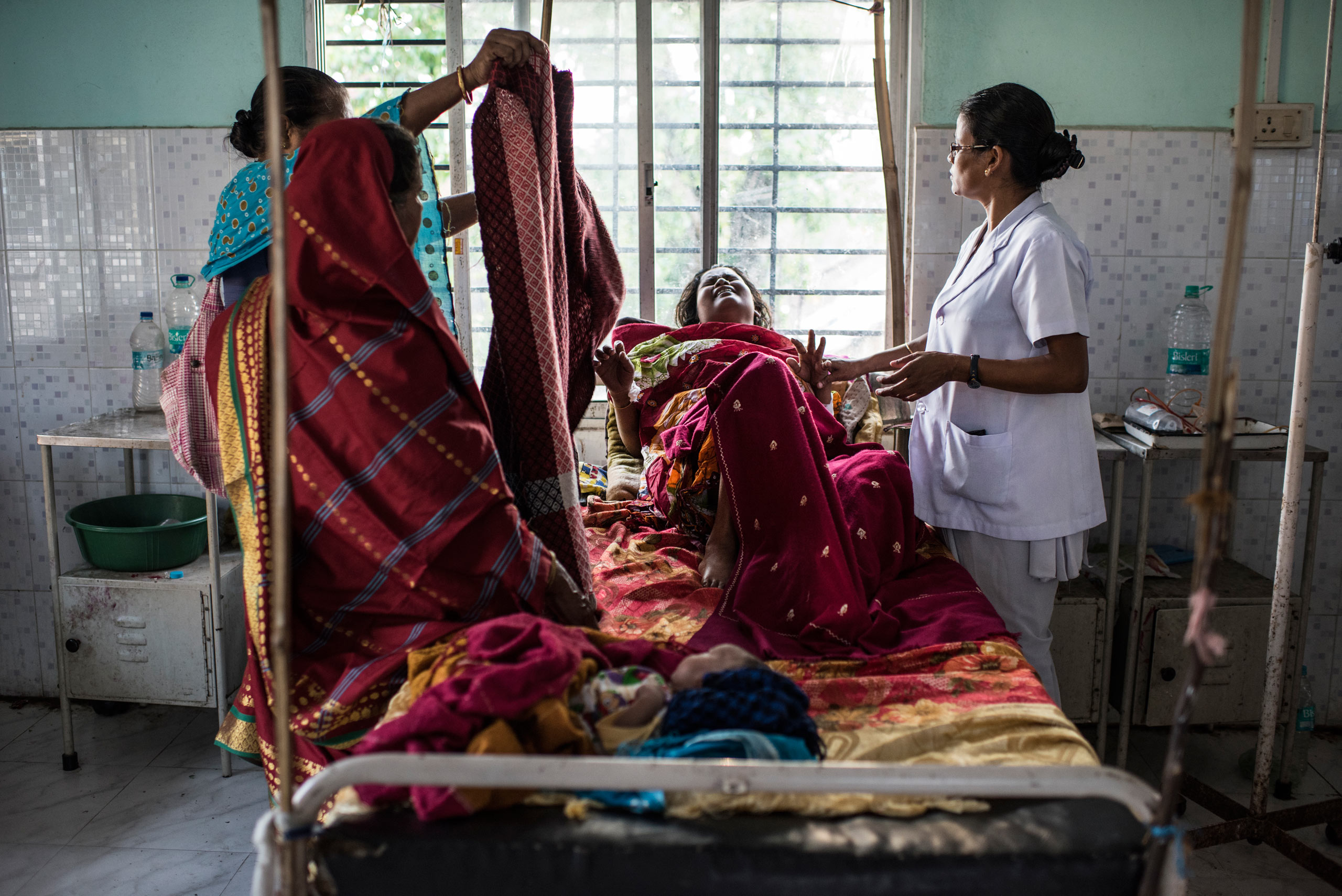 Nazreen Khatoon winces in pain as she lies gravely ill, suffering from severe postpartum anemia at the Tezpur Civil Hospital in Tezpur, Assam, India. April 2015.