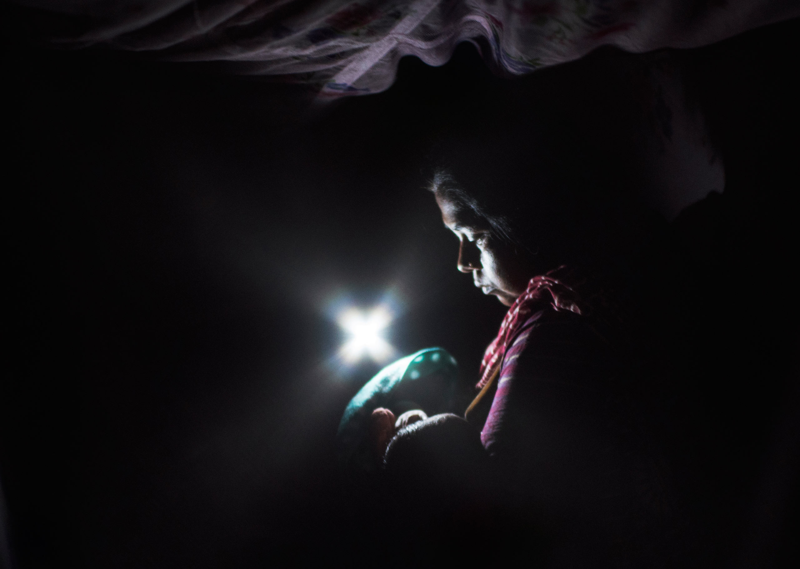 Nasuran Begham, 30, sits in the dark during an electricity cut holding her third child, four days after giving birth, in the a postnatal ward. Assam, India. April, 2015.