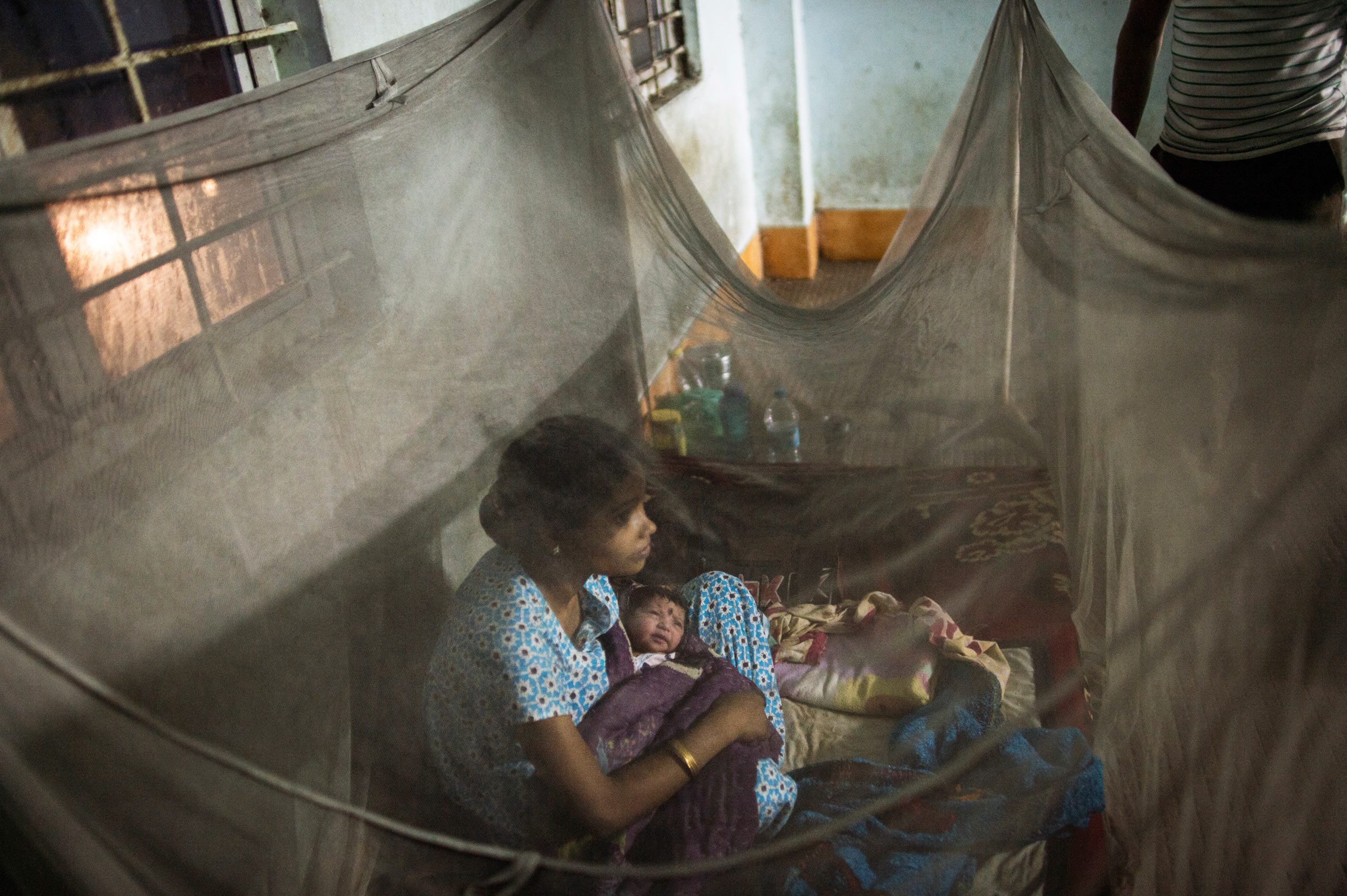 Indian families sleep outside a postnatal ward, where women are in labor and recovering from delivery,  accompanied by their families. Tezpur Civil Hospital, Tezpur, Assam, India. April, 2015.