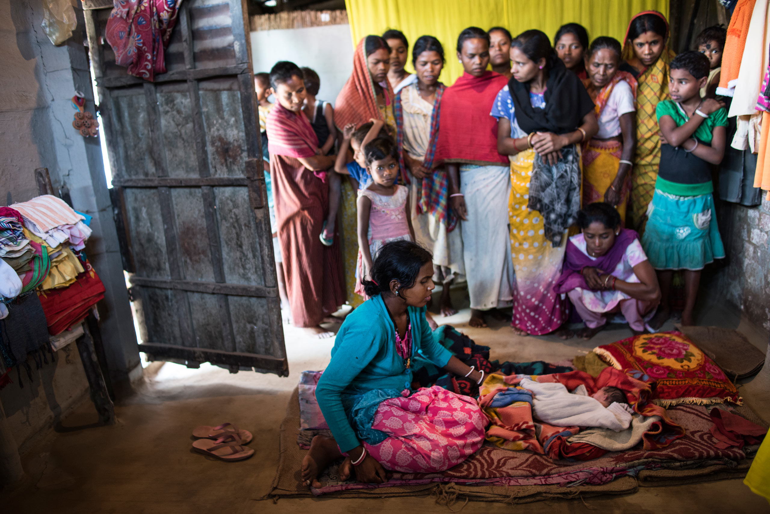 Resonate Bhumi sits over her severely deformed infant hours after giving birth at home, in the village of Holing Kata, in the Tinkharia plantation.  Bhumi's son was born with no arms and a cleft palate. Many women from the village came to look at the mother and child. Assam, India. April 8, 2015.