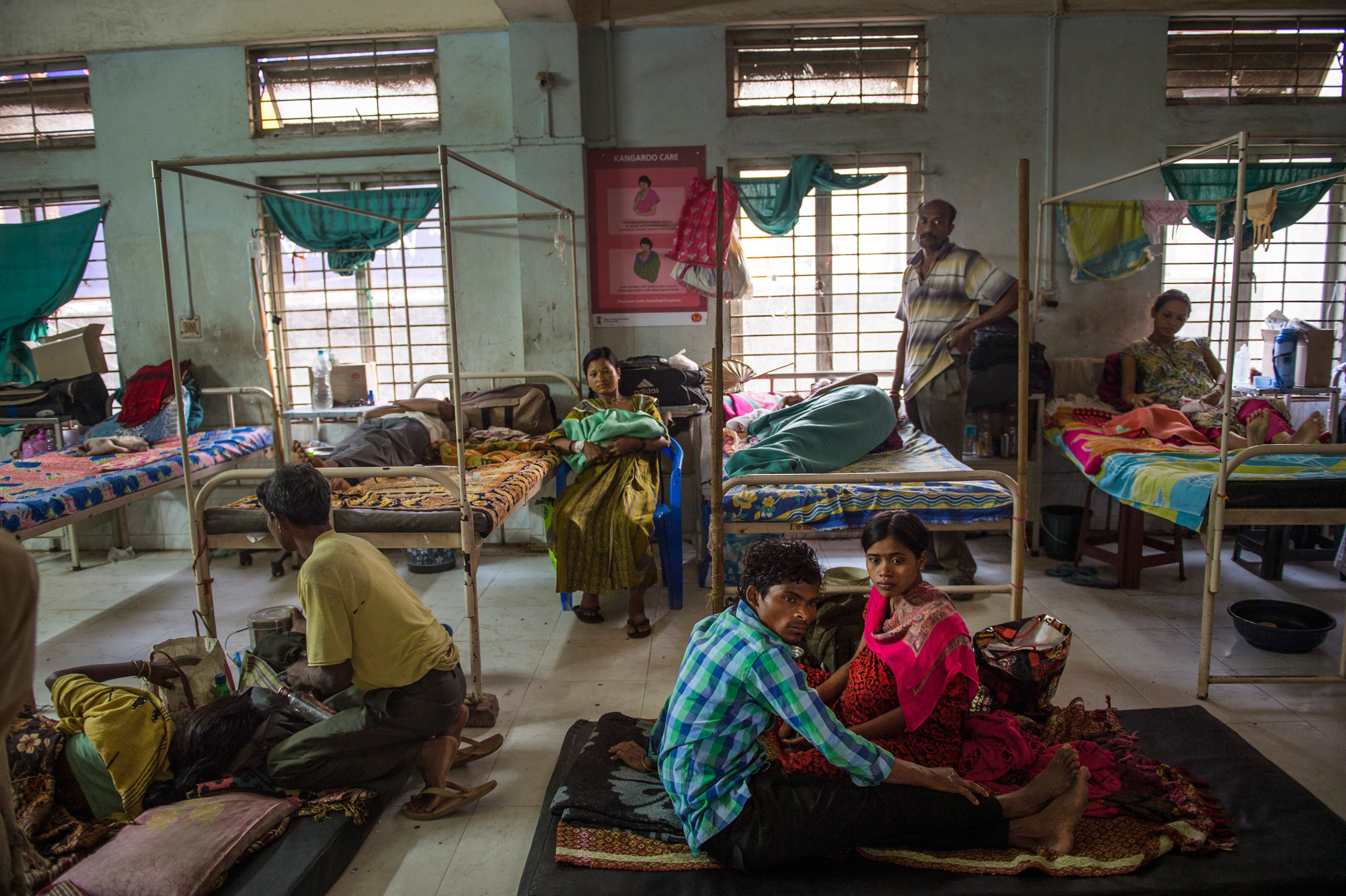 Indian families rest in a room reserved for women recovering from cesarean sections, at the Tezpur Civil Hospital in Tezpur, Assam, India. April, 2015.  Assam has the highest rate of women dying in childbirth and from pregnancy-related causes in all of India. The conditions in many of Assam's state-run medical facilities are often overcrowded and unhygienic, with an insufficient number of doctors, and patients sprawled out in the floors and hallways due to a limited number of beds.