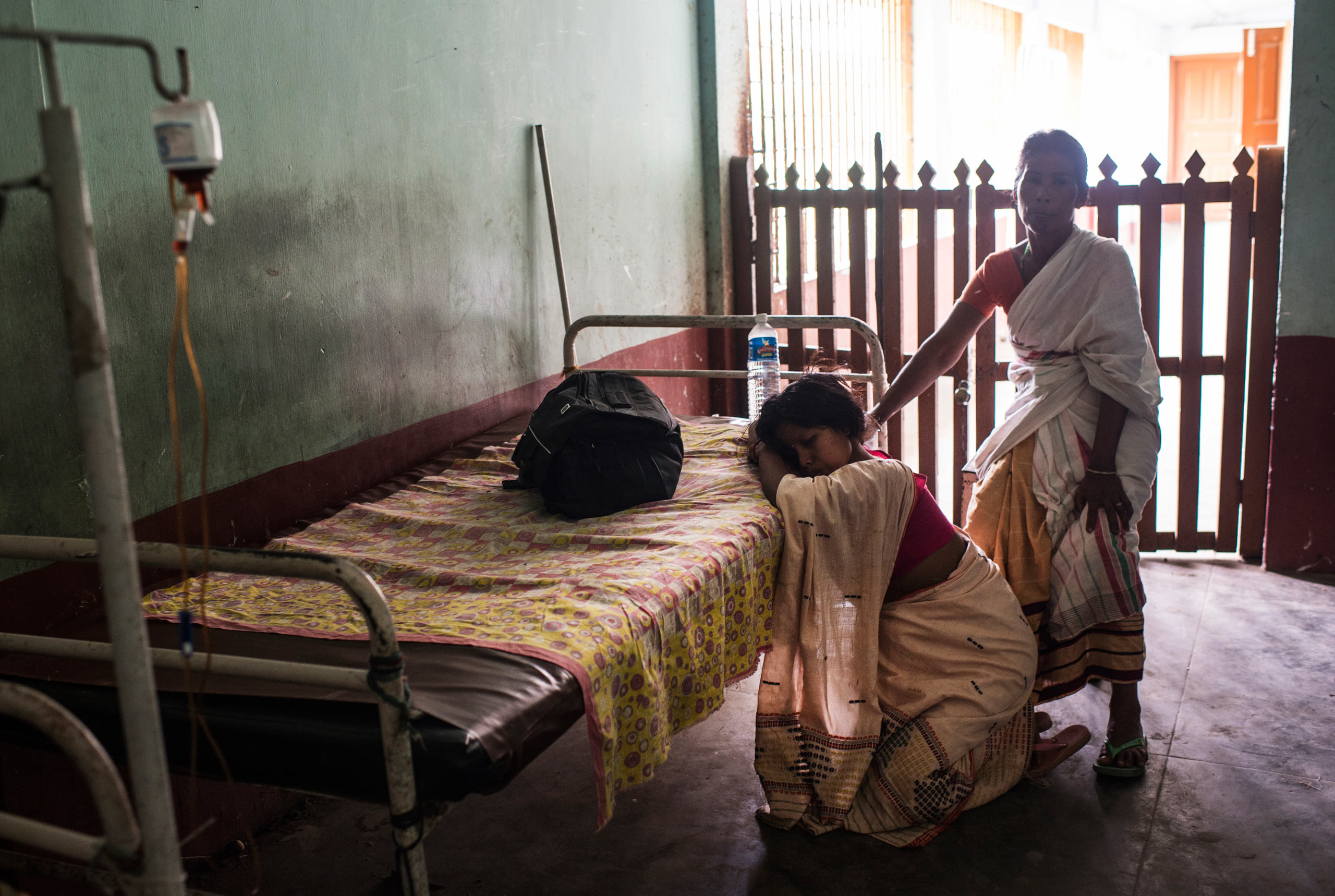 A young woman kneels with labor pains in the hallway of the maternity ward at the Dhekiajuli Community Health Center in Assam, India. April 8, 2015.