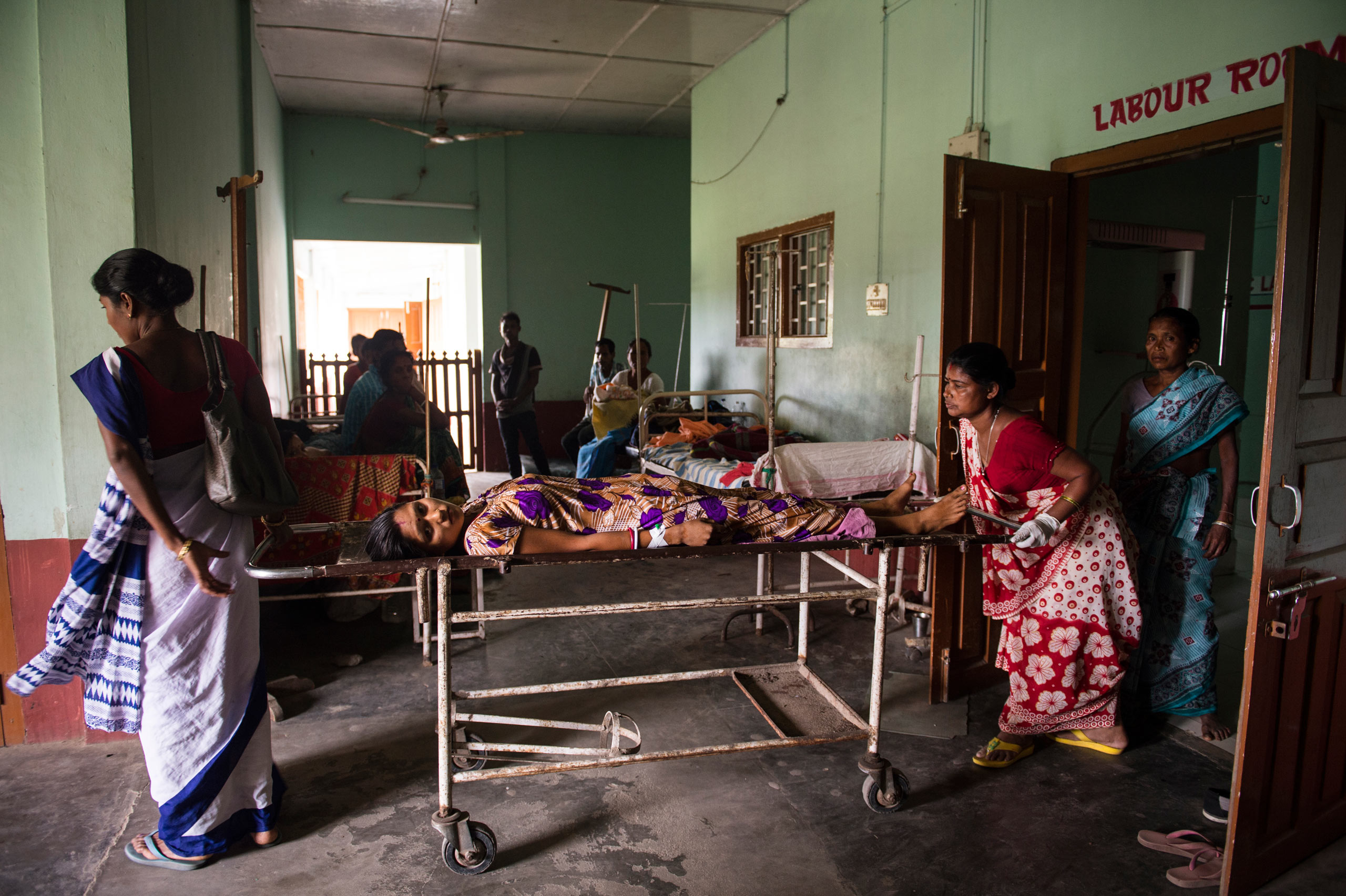 Sarasoti Bauri, 22, lies on a stretcher after she delivered her second child in a taxi en route to the hospital. She lost a relevant amount of blood prior to arriving at the Dhekiajuli Community Health Center in Assam, India. April 8, 2015.
