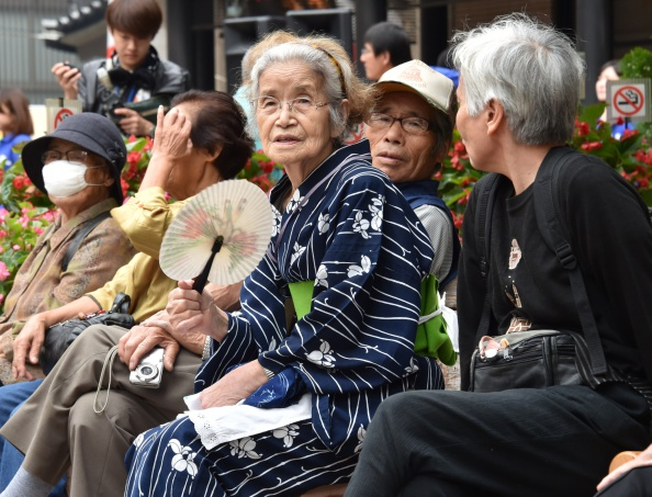 Elderly residents rest in the grounds of a temple in Tokyo on Sept. 15, 2014, as the country marks Respect for the Aged Day