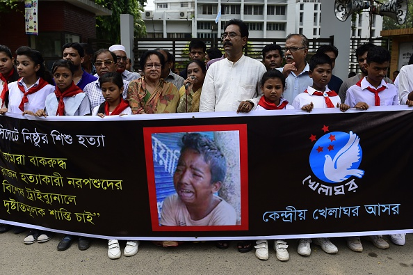 Bangladeshi protesters carry a banner during a demonstration against the lynching of a 13-year-old boy in Dhaka on July 14, 2015
