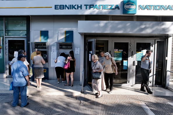 People queue to get money from ATMs as Greek banks reopened on Monday morning after three weeks of closure on July 20, 2015 in Athens, Greece