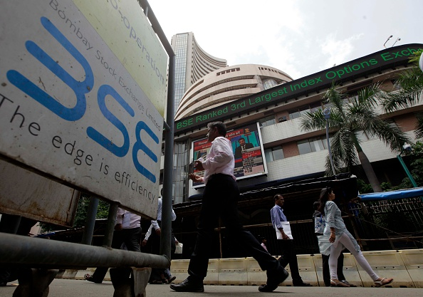 People walk outside the Bombay Stock Exchange on Aug. 24, 2015