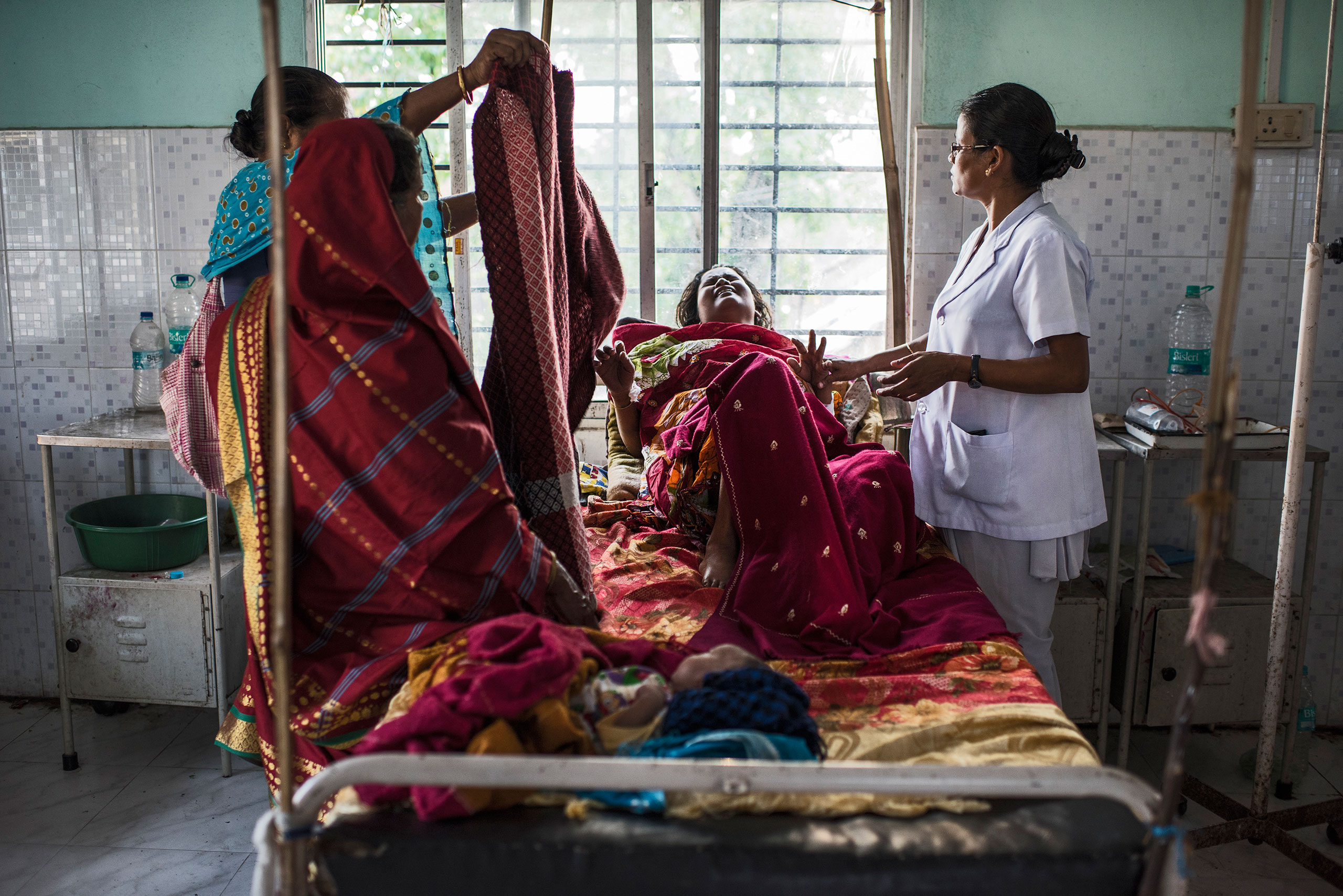 Nazreen Khatoon winces in pain as she lies gravely ill, suffering from severe postpartum anemia at the Tezpur Civil Hospital in Tezpur, Assam, India. April 2015. From  Where Childbirth Can Mean Death