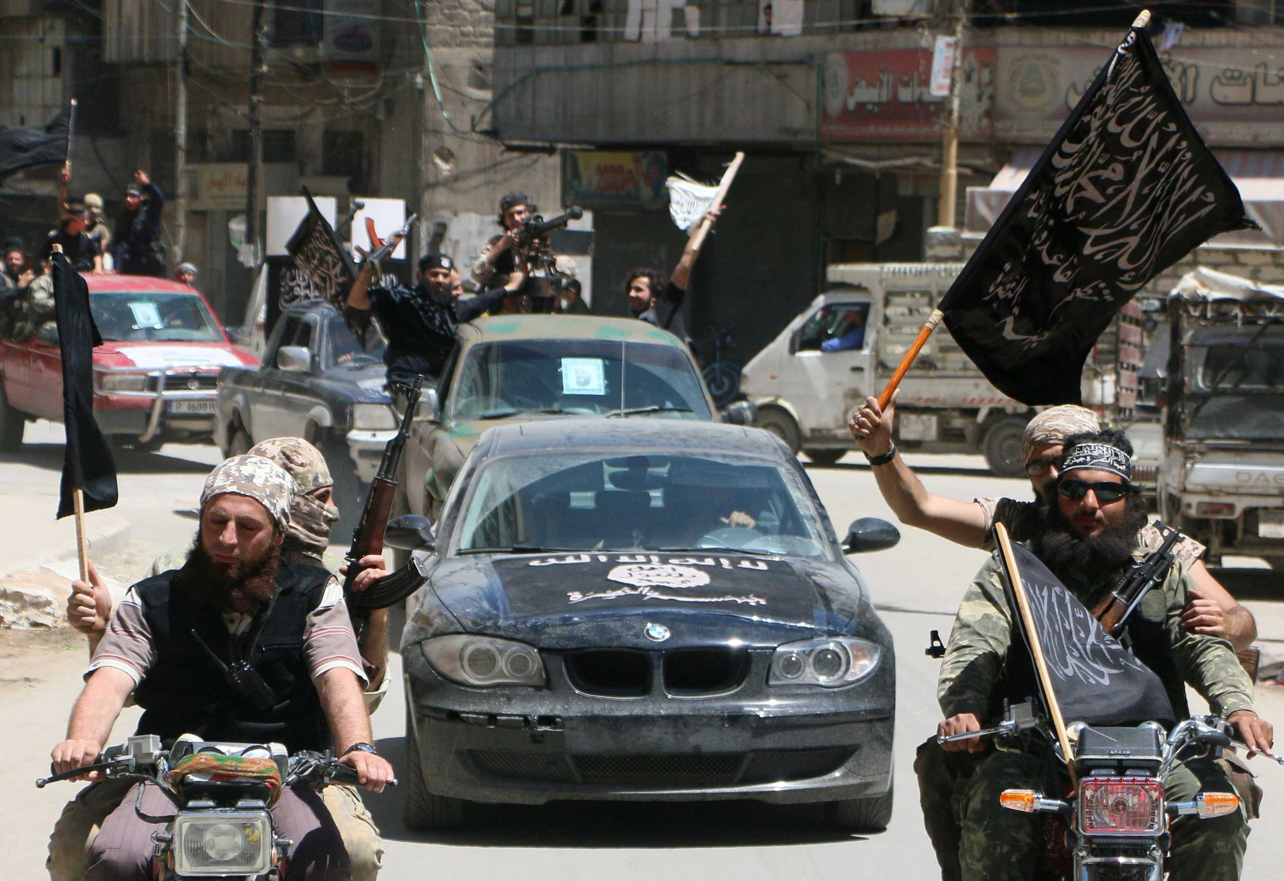 Fighters from Al-Qaeda's Syrian affiliate Al-Nusra Front drive in the northern Syrian city of Aleppo flying Islamist flags as they head to a frontline, on May 26, 2015.