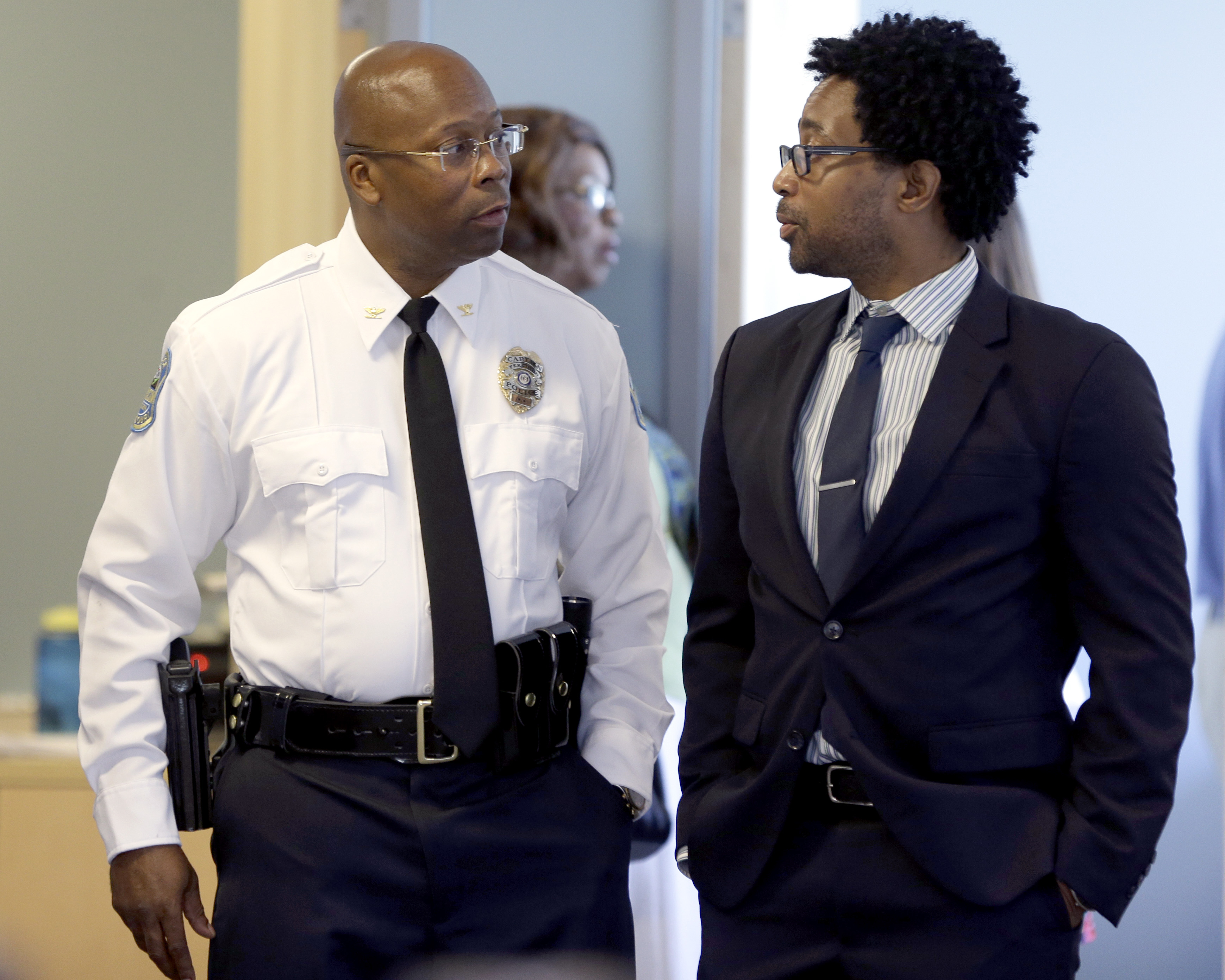Andre Anderson, left, speaks with Ferguson City Council member Wesley Bell after being introduced as the the interim chief of the Ferguson Police Department during a news conference on July 22, 2015, in Ferguson, Mo.