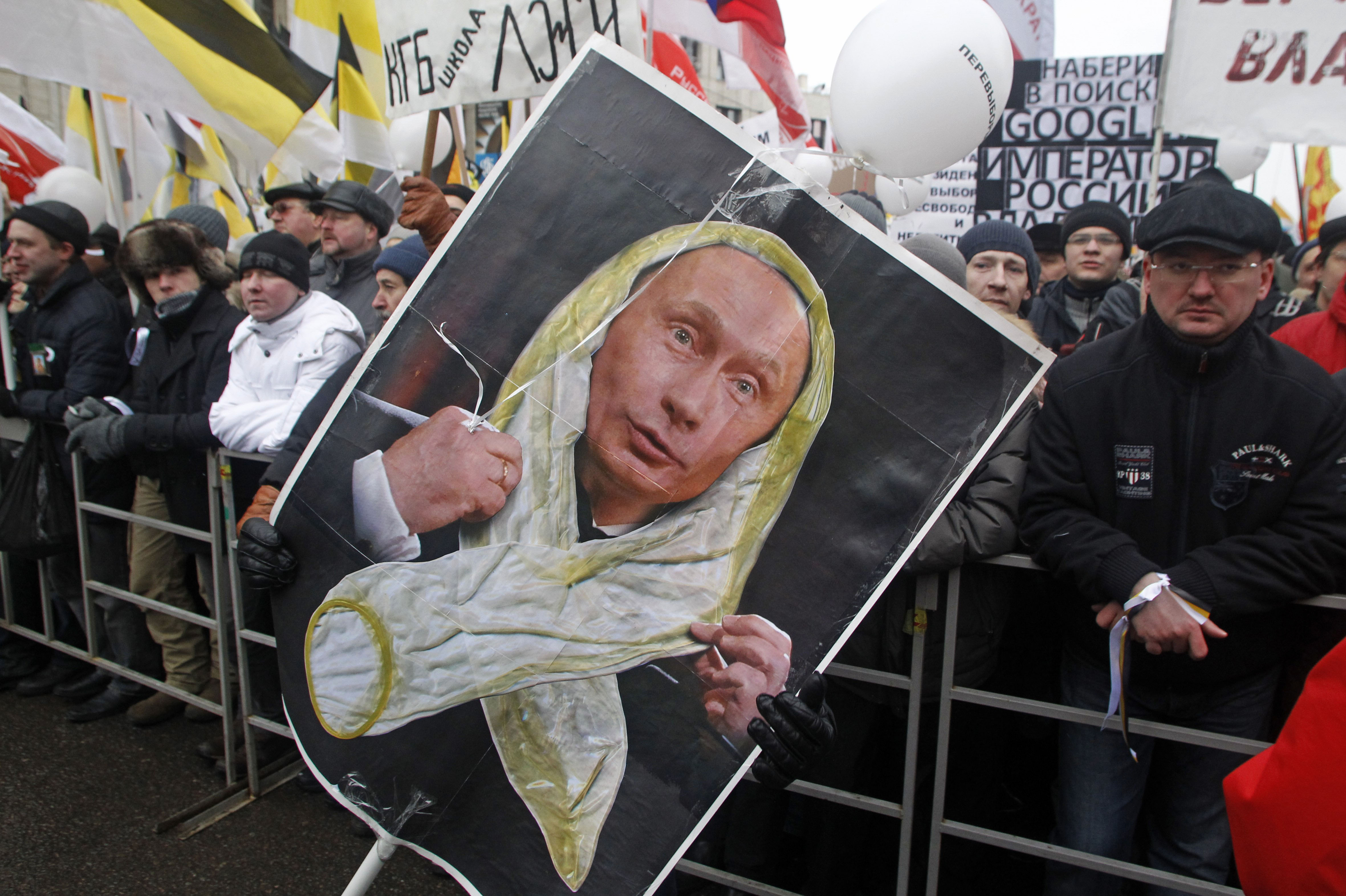 This is  a  Saturday, Dec. 24, 2011 file photo of  protesters holding a portrait of Russian Prime Minister Vladimir Putin changed by an unidentified satirical artist to show him wearing a condom, during a protest against alleged vote rigging in Russia's parliamentary elections in Moscow, Russia