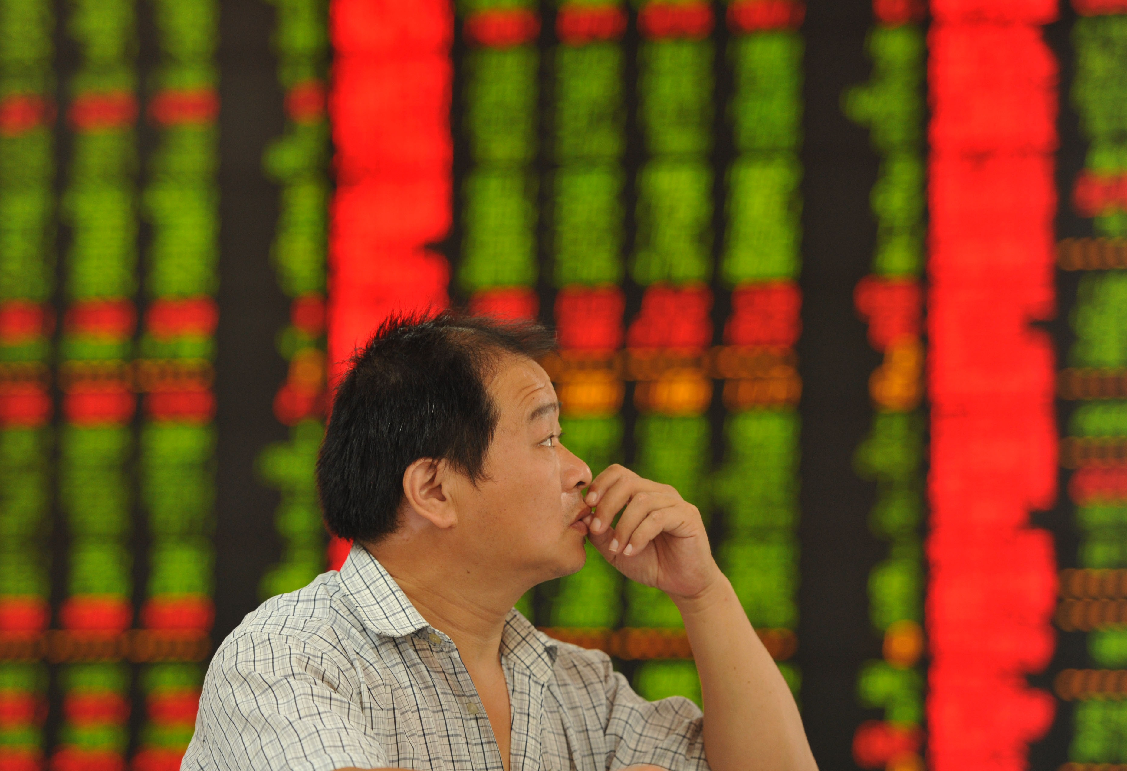 A concerned Chinese investor looks at prices of shares (red for price rising and green for price falling) at a Chinese stock brokerage house on August 5, 2015.