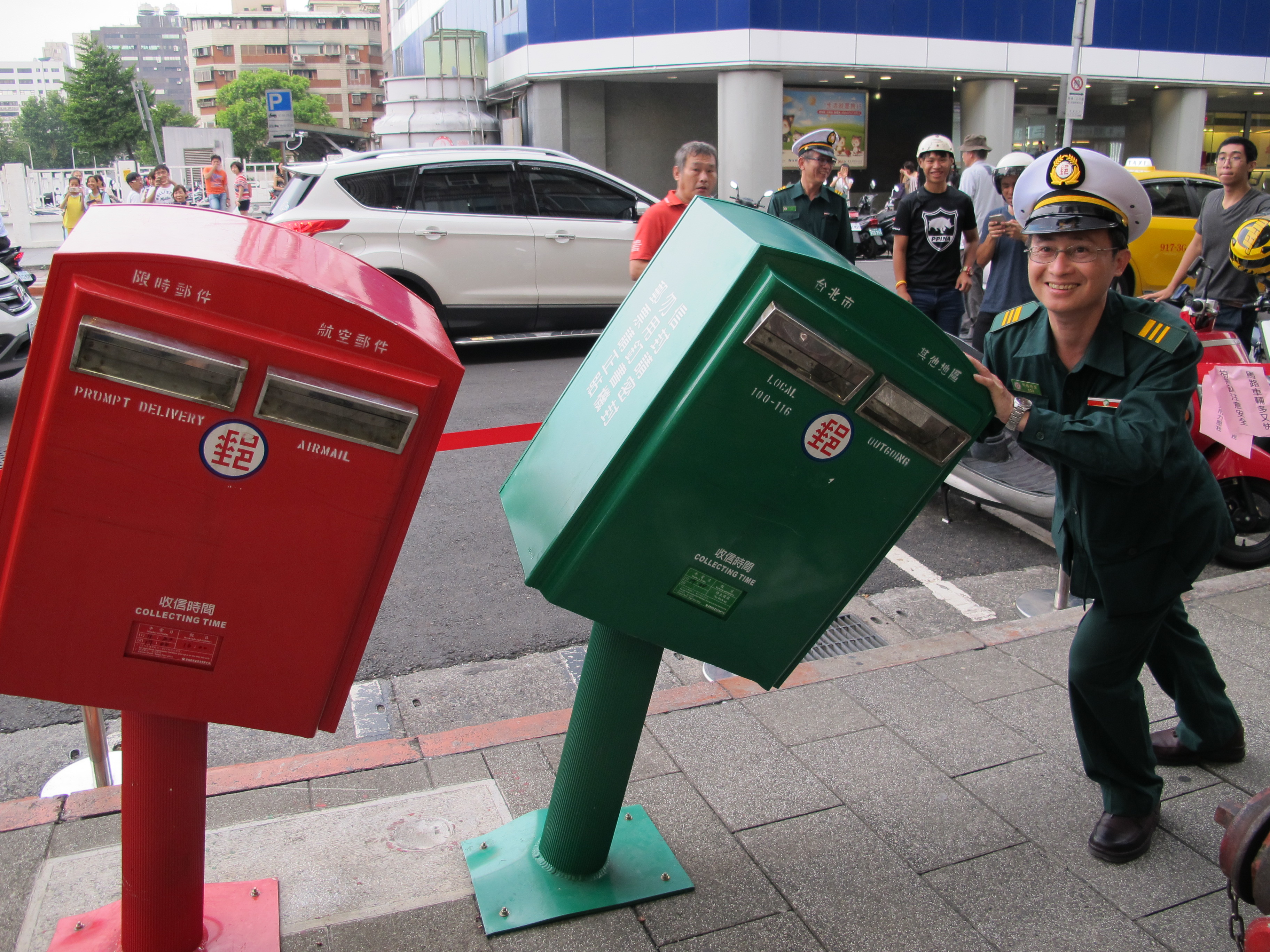 A postman poses in front of a pair of newly famous postal boxes in Taipei on August 10, 2015