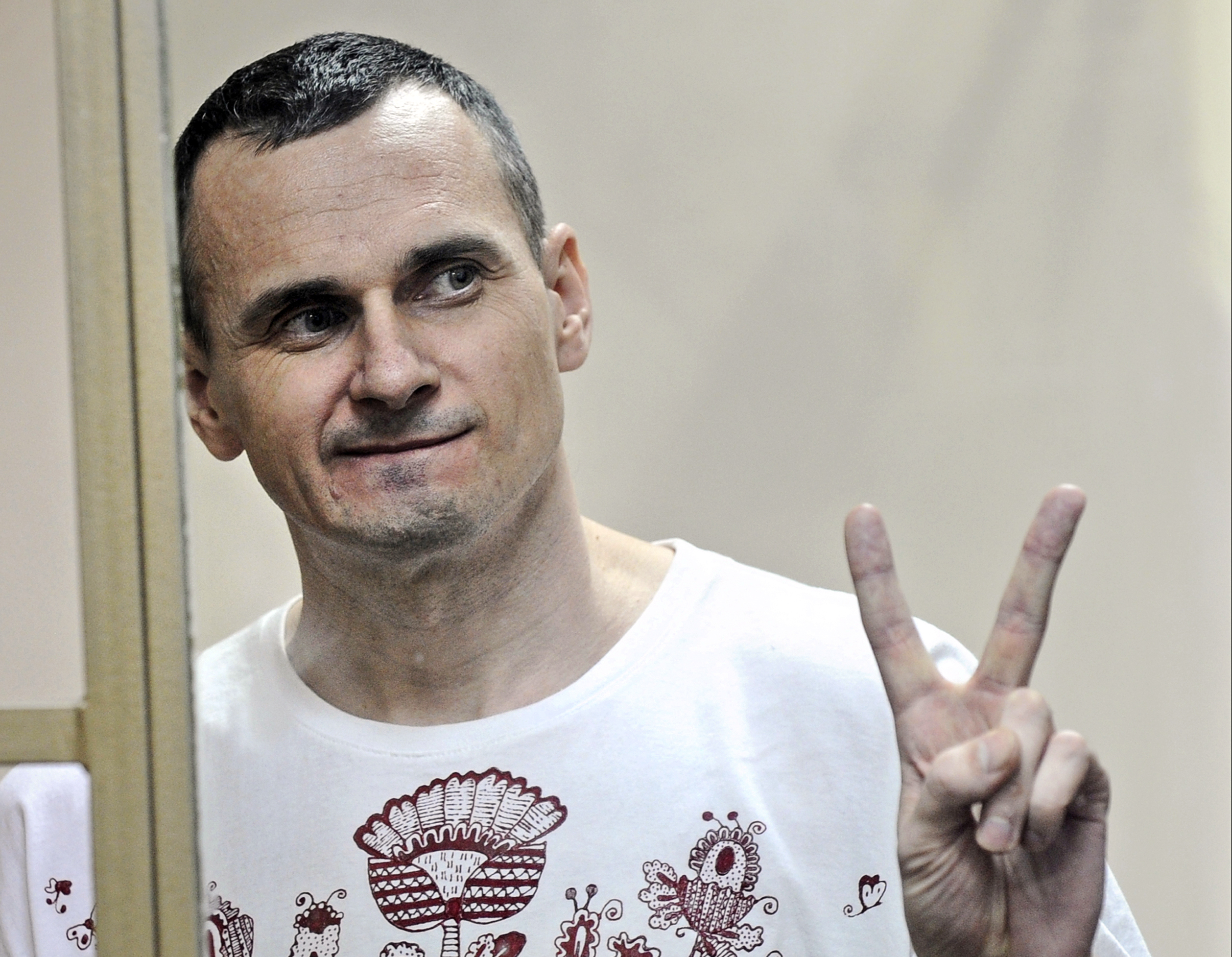 Oleg Sentsov gestures as the verdict is delivered, as he stands behind bars at a court in Rostov-on-Don, Russia, on Aug. 25, 2015