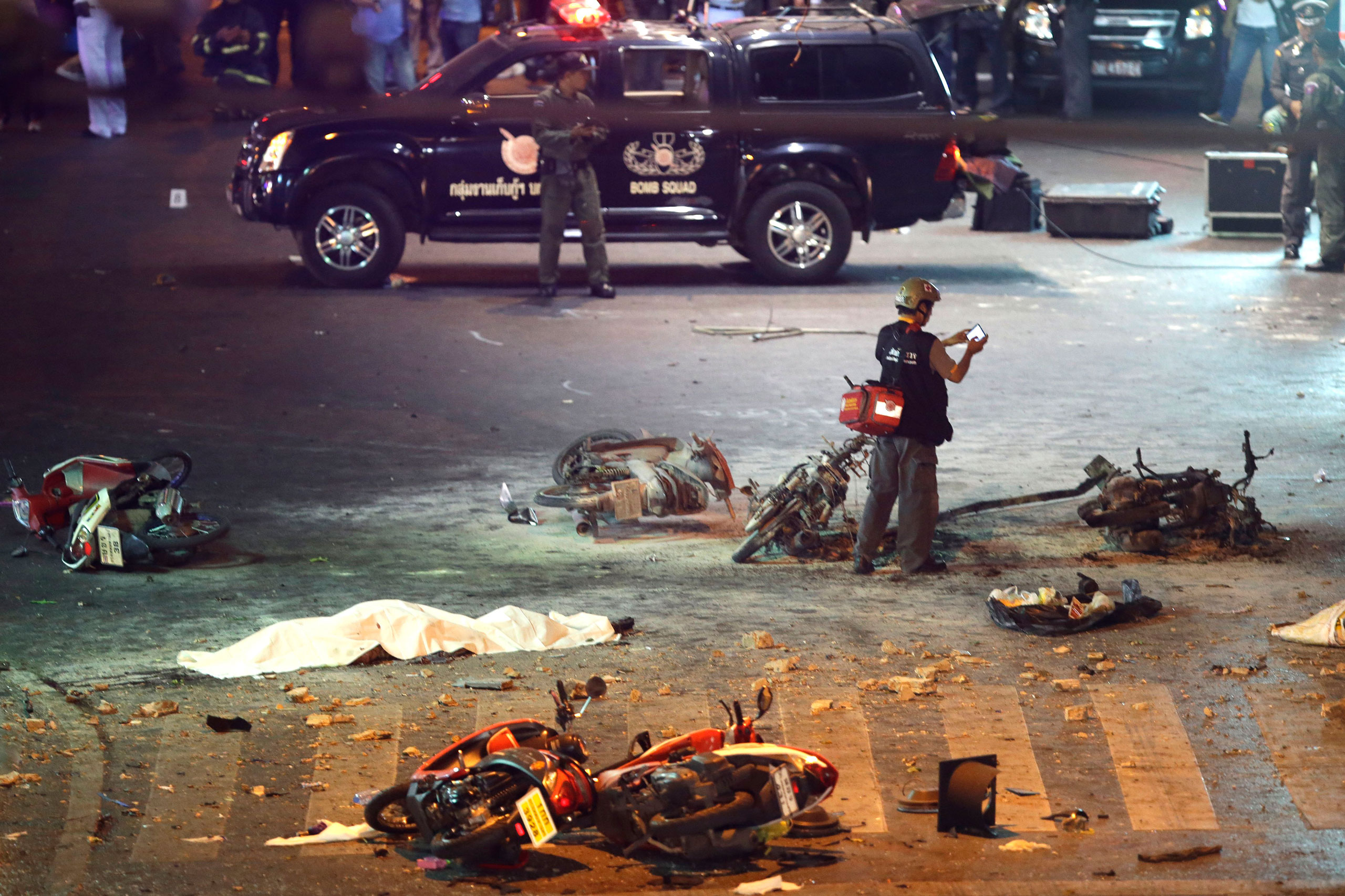 A policeman photographs debris from an explosion in central Bangkok, Thailand, on Aug. 17, 2015.
