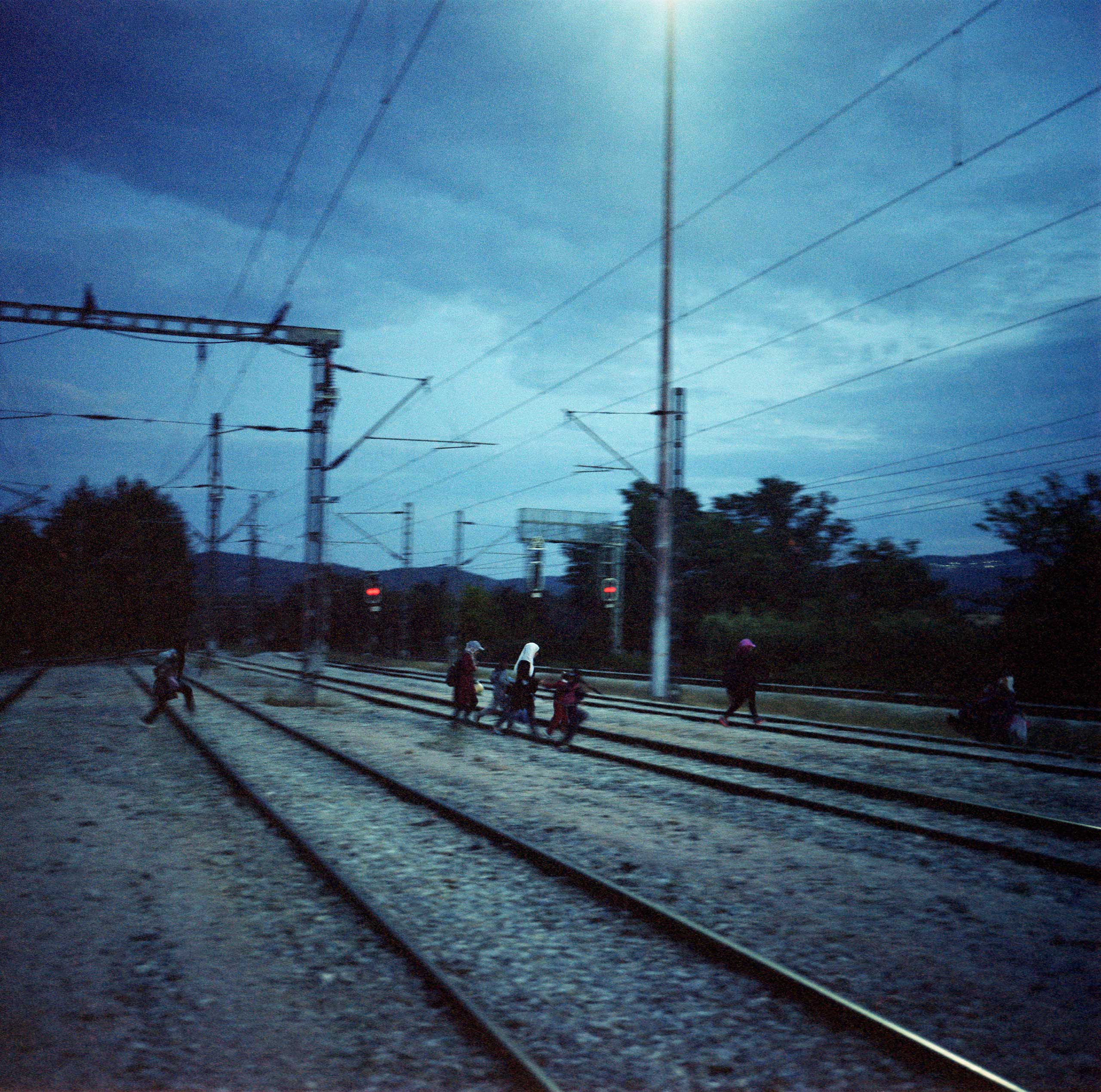 Refugees walking across train tracks in Idomeni, a border town in Northern Greece. June 2015.