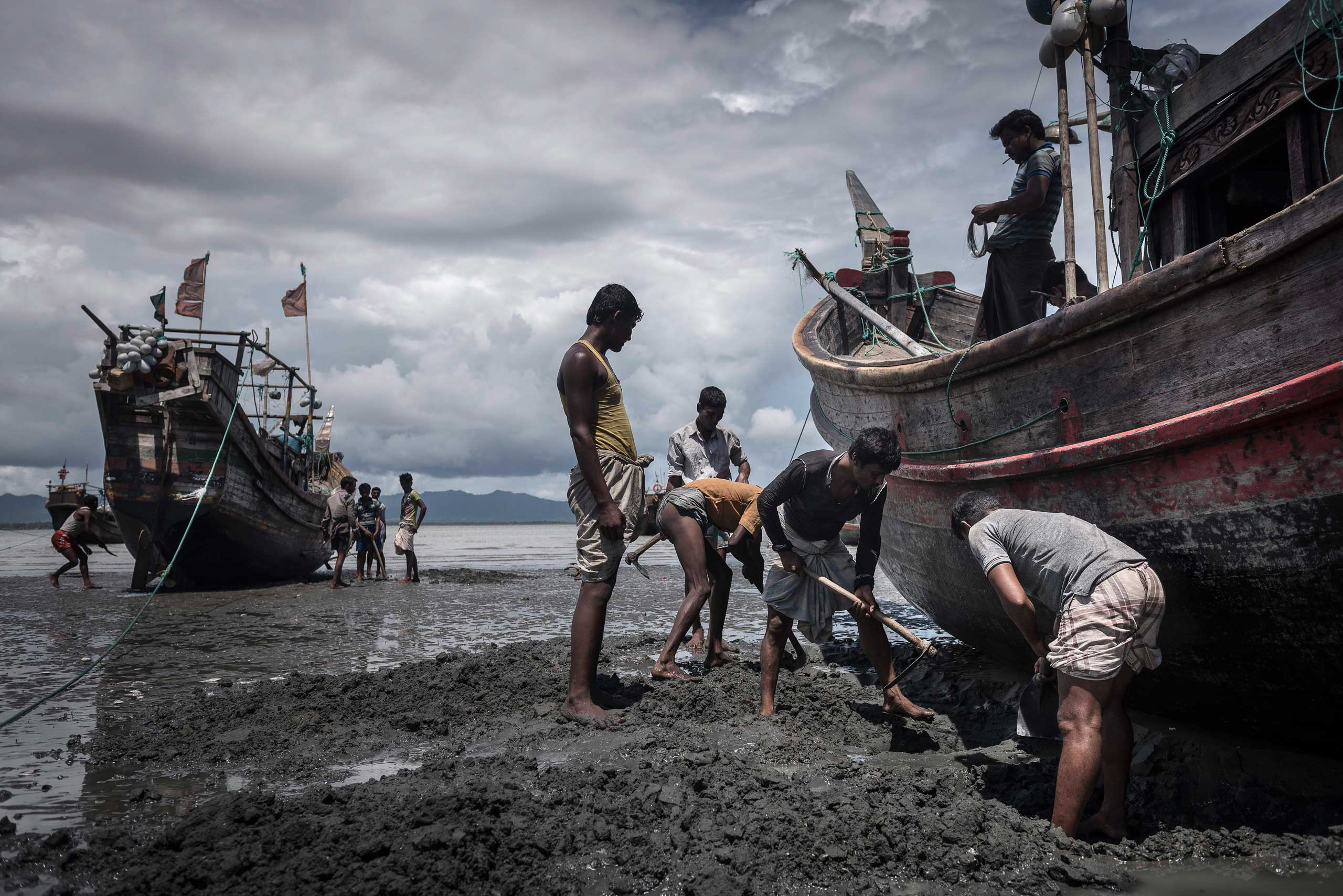 The New York Times: A Bangladeshi Town in                               Human Trafficking's Grip                               Fishermen dig their boats from the mud while awaiting a high tide in Shah Porir Dwip, Bangladesh, on June 17, 2015.