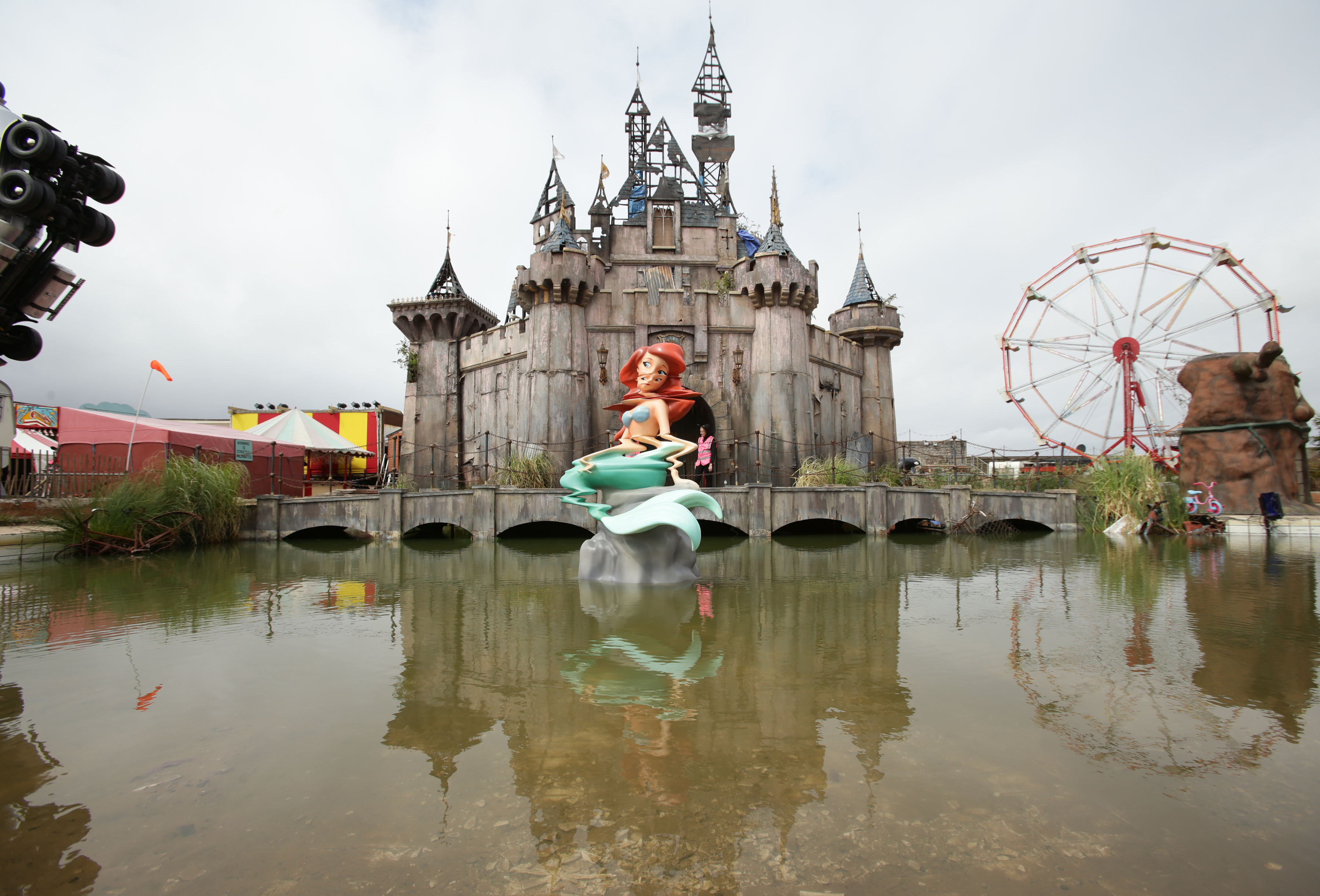 A mermaid piece by Banksy, with a castle by Banksy and Block 9 in the background, during the press preview for the artist's biggest show to date on Aug. 20, 2015, entitled Dismaland, at Tropicana in Western-super-Mare, Somerset.