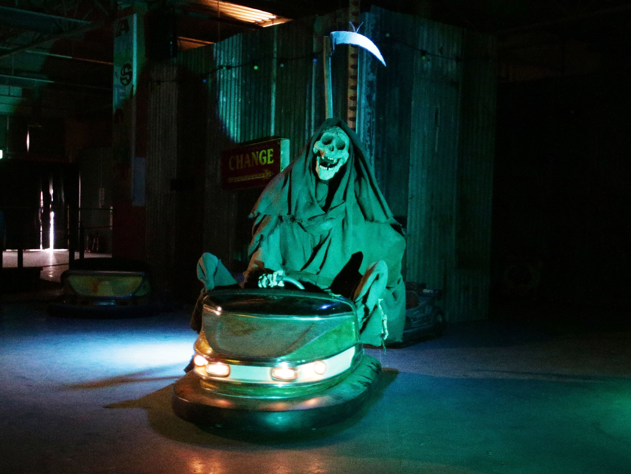 A sculpture of the grim reaper in a bumper car.