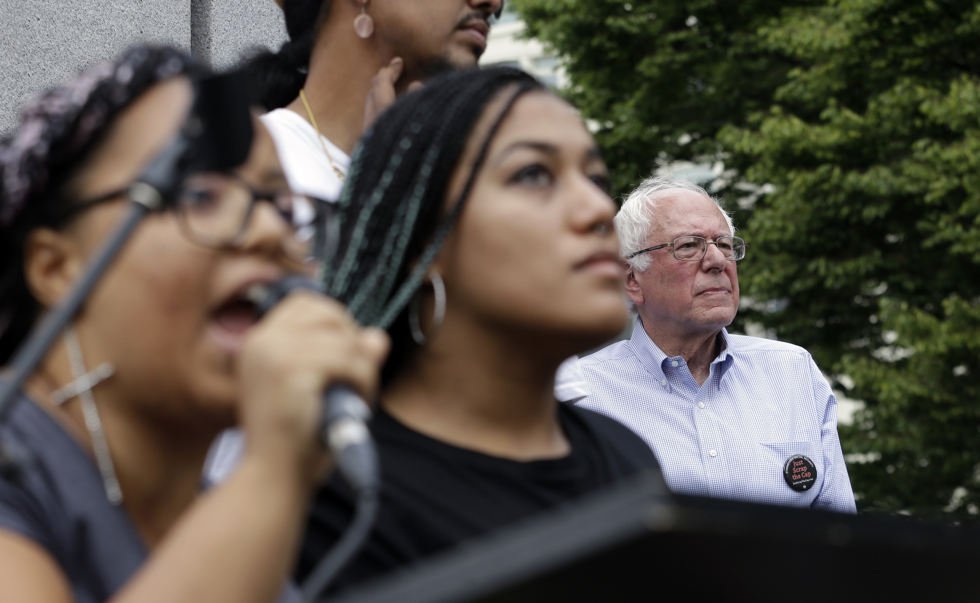 Marissa Johnson, left, speaks as Mara Jacqueline Willaford stands with her and Democratic presidential candidate Sen. Bernie Sanders, I-Vt., stands nearby as the two women take over the microphone at a rally on Aug. 8, 2015, in downtown Seattle.