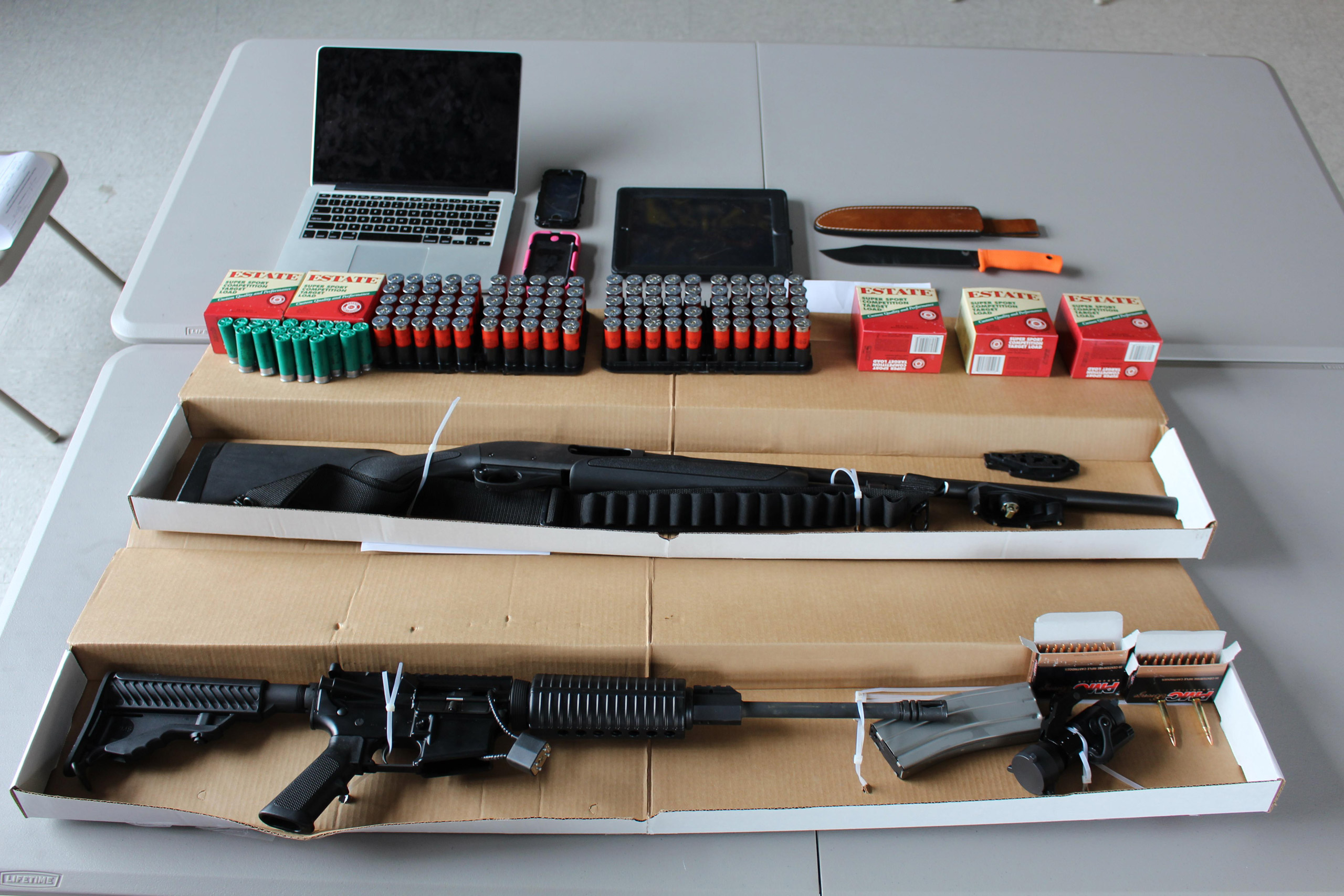 This photo, provided by the Boston Police Department, shows a 12-gauge Remington shotgun, a DPM5 Model AR-15 rifle, several hundred rounds of ammunition, and a hunting knife, confiscated by the police in Boston on Aug. 21, 2015.