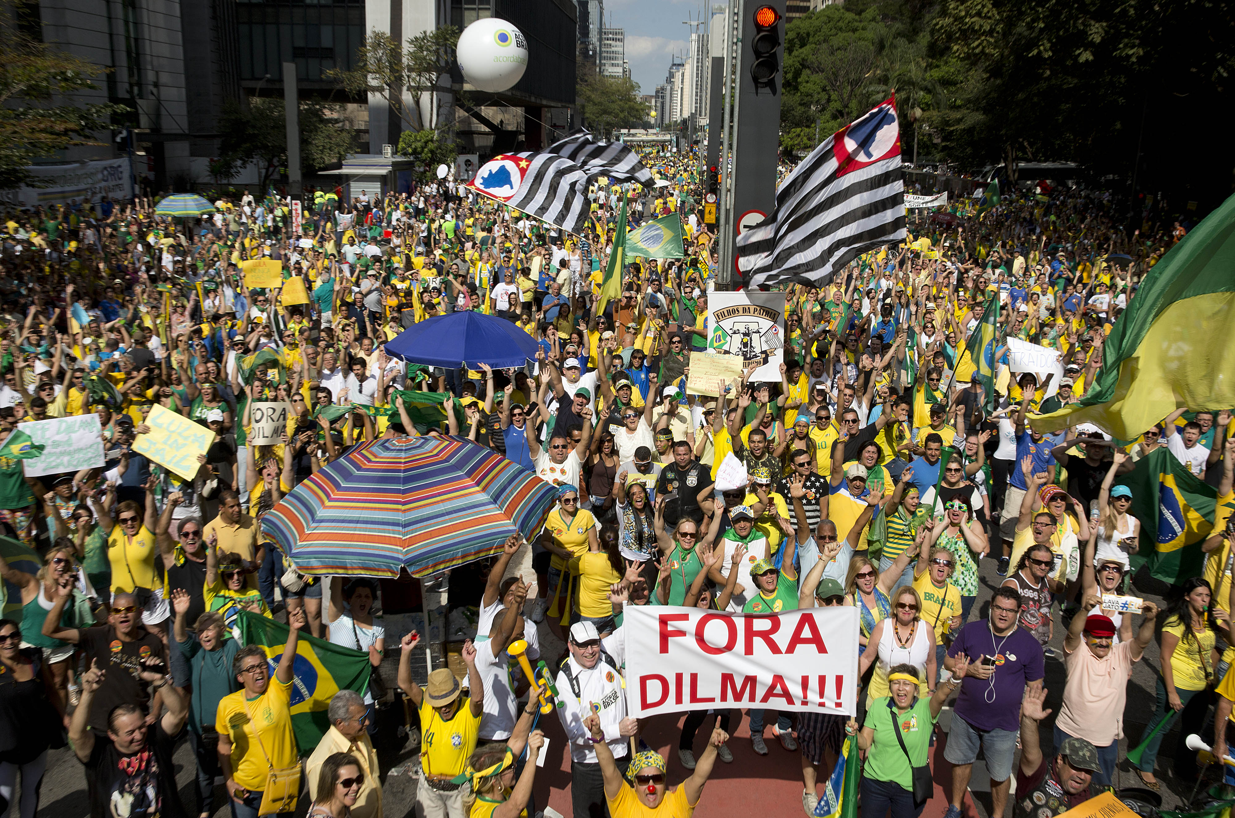Demonstrators hold a sign that reads in Portuguese  Dilma out  during a protest demanding the impeachment of Brazil's President Dilma Rousseff in Sao Paulo, Brazil, Aug. 16, 2015