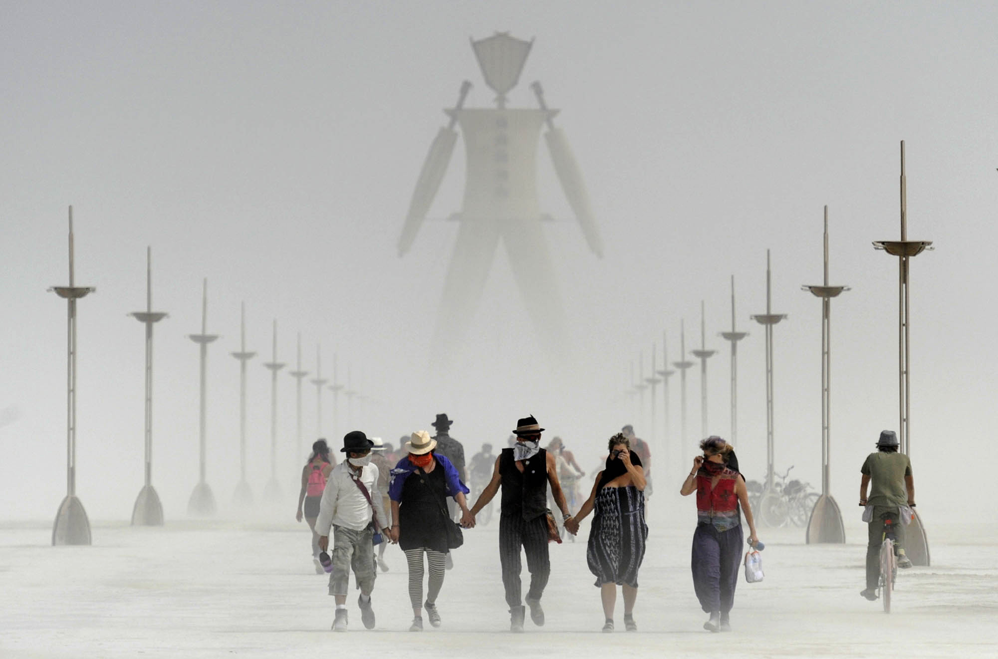 Participants walk through dust at the annual Burning Man event in the Black Rock Desert of Gerlach, Nev., on Aug. 29, 2014.