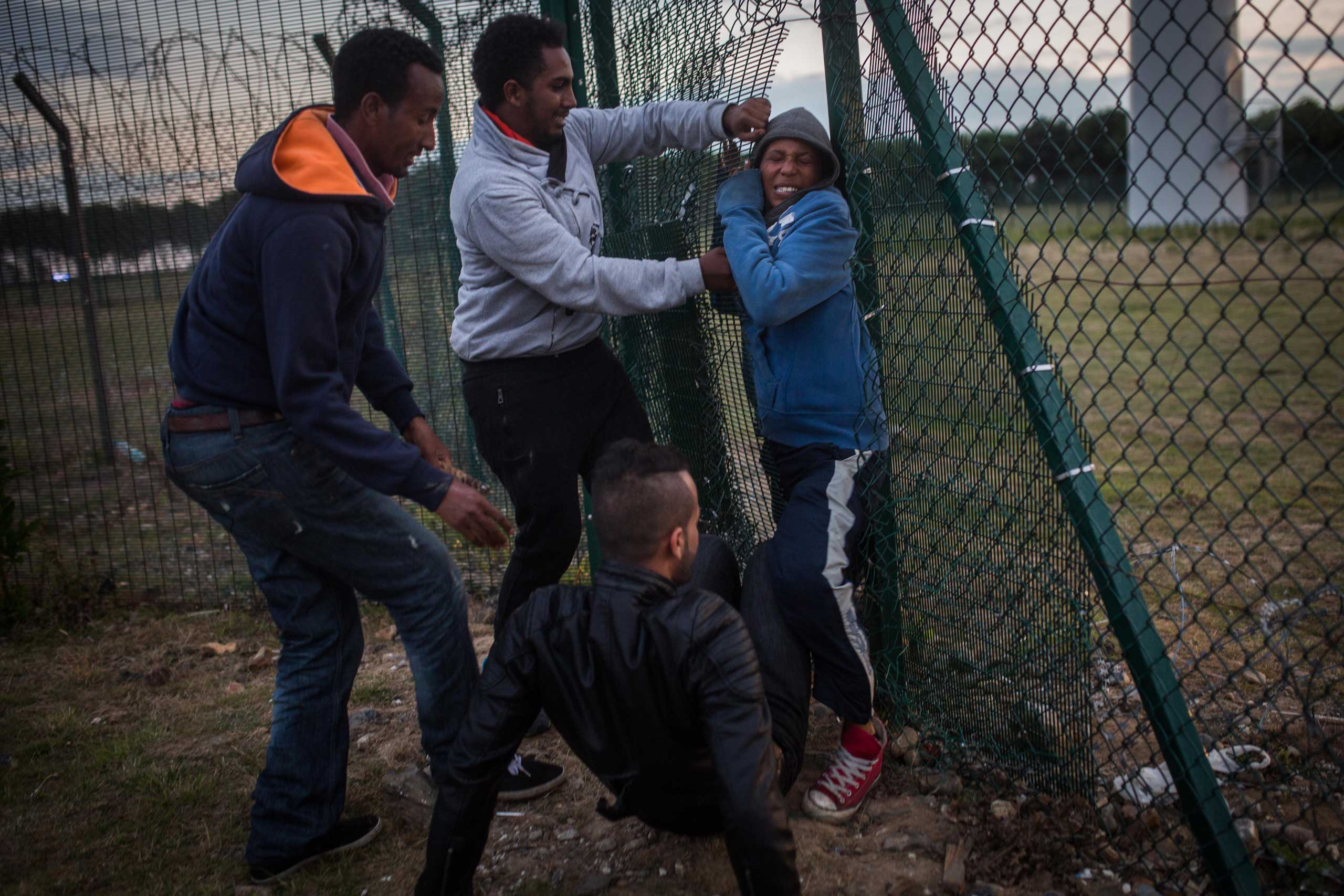 People help a young man squeeze through a gap in a fence near the Eurotunnel terminal in Coquelles in Calais, on July 30, 2015.