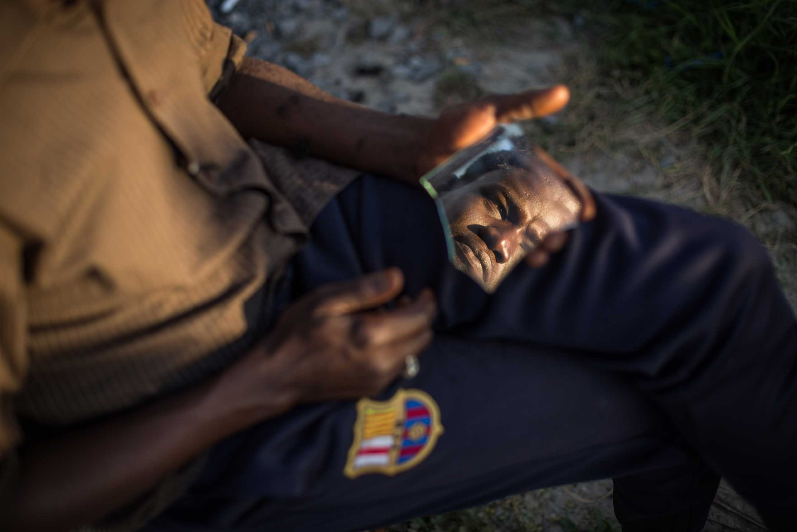 A Sudanese man is seen in a piece of broken mirror whilst having his hair cut in a make shift camp near the port of Calais,  on Aug. 2, 2015.