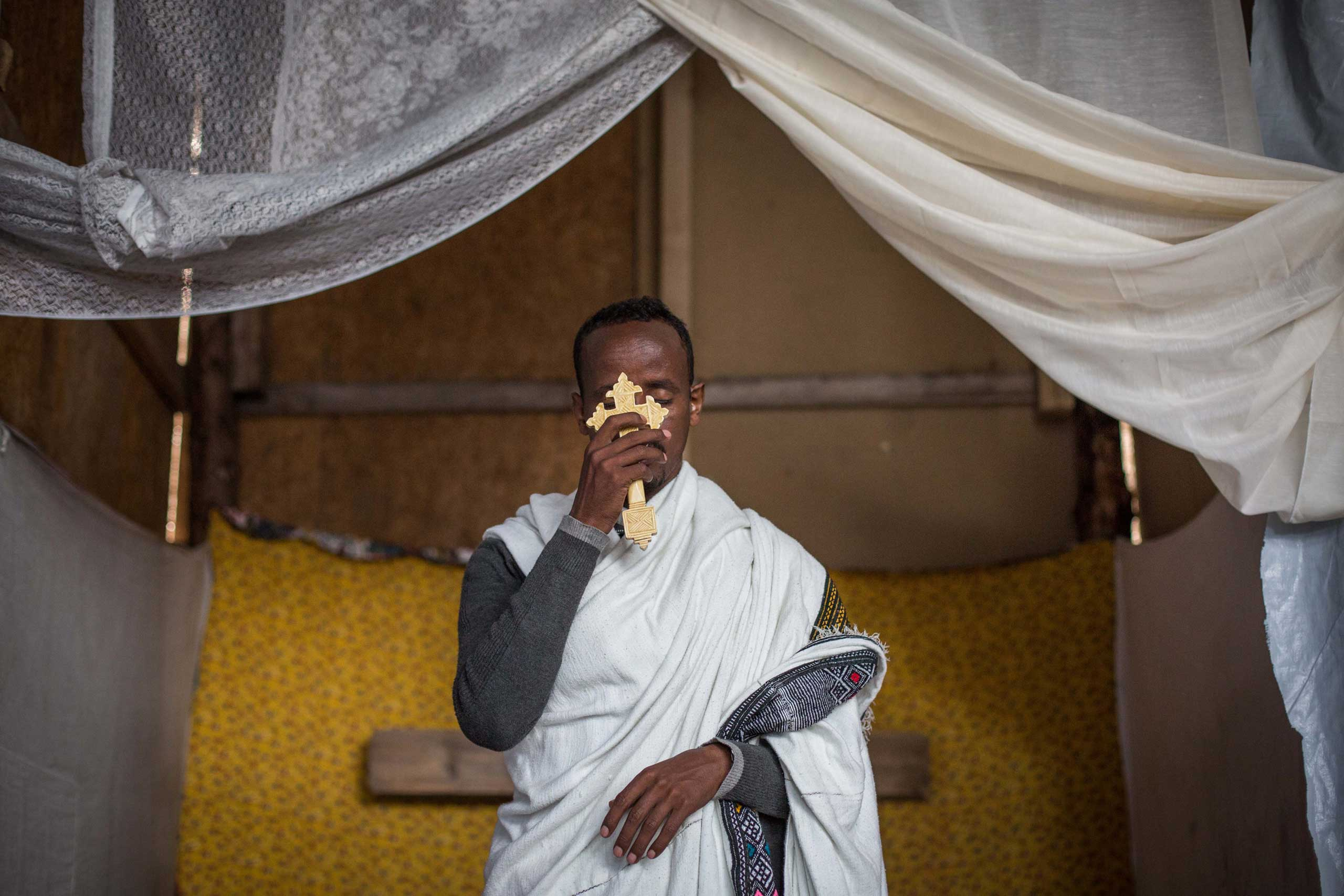 Kibrom Kasta leads an Orthodox service for Ethiopian and Eritrean worshippers at a church in a make shift camp near the port of Calais, on Aug. 2, 2015.