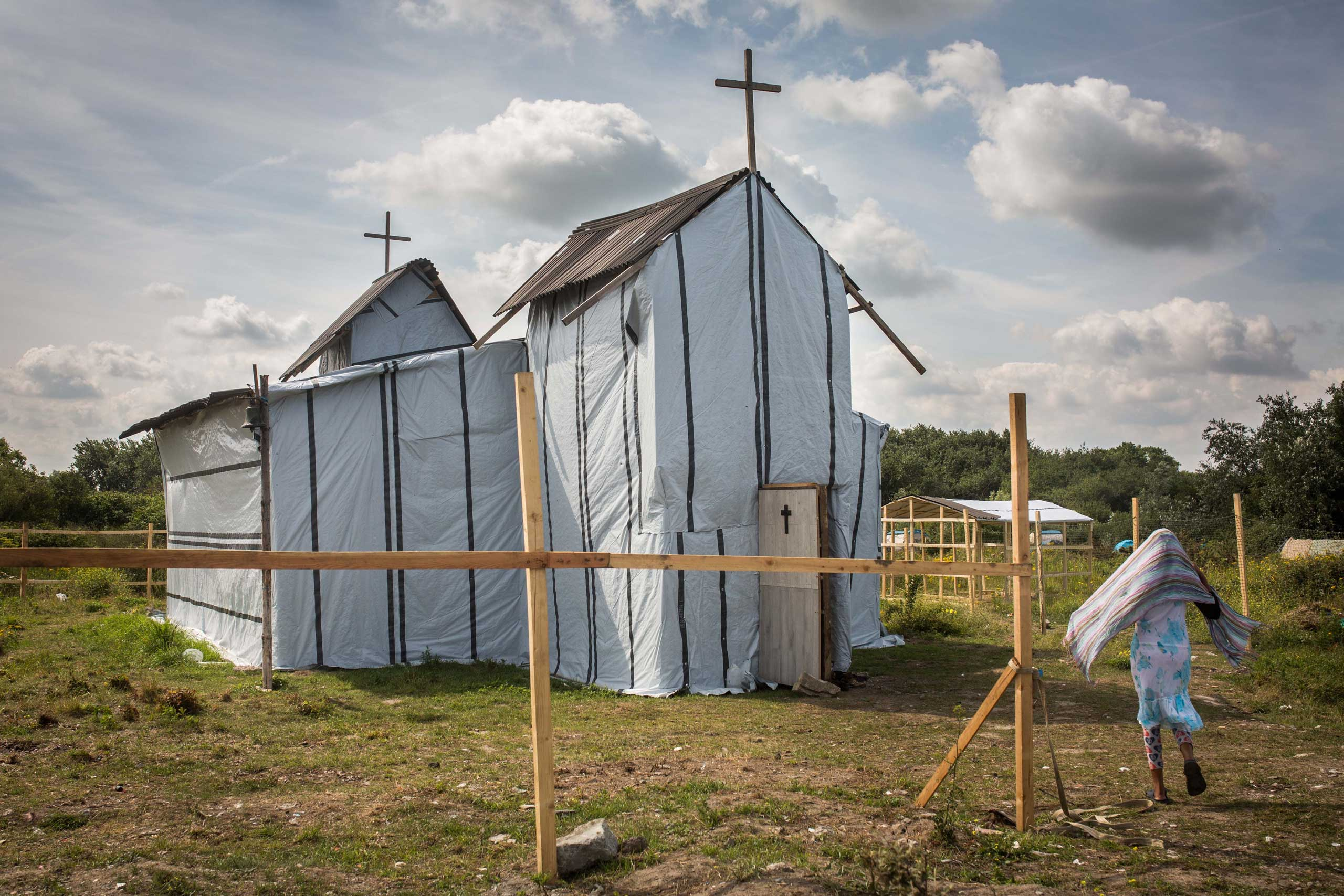A woman enters the site of a church in a make shift camp near the port of Calais, on July 31, 2015.