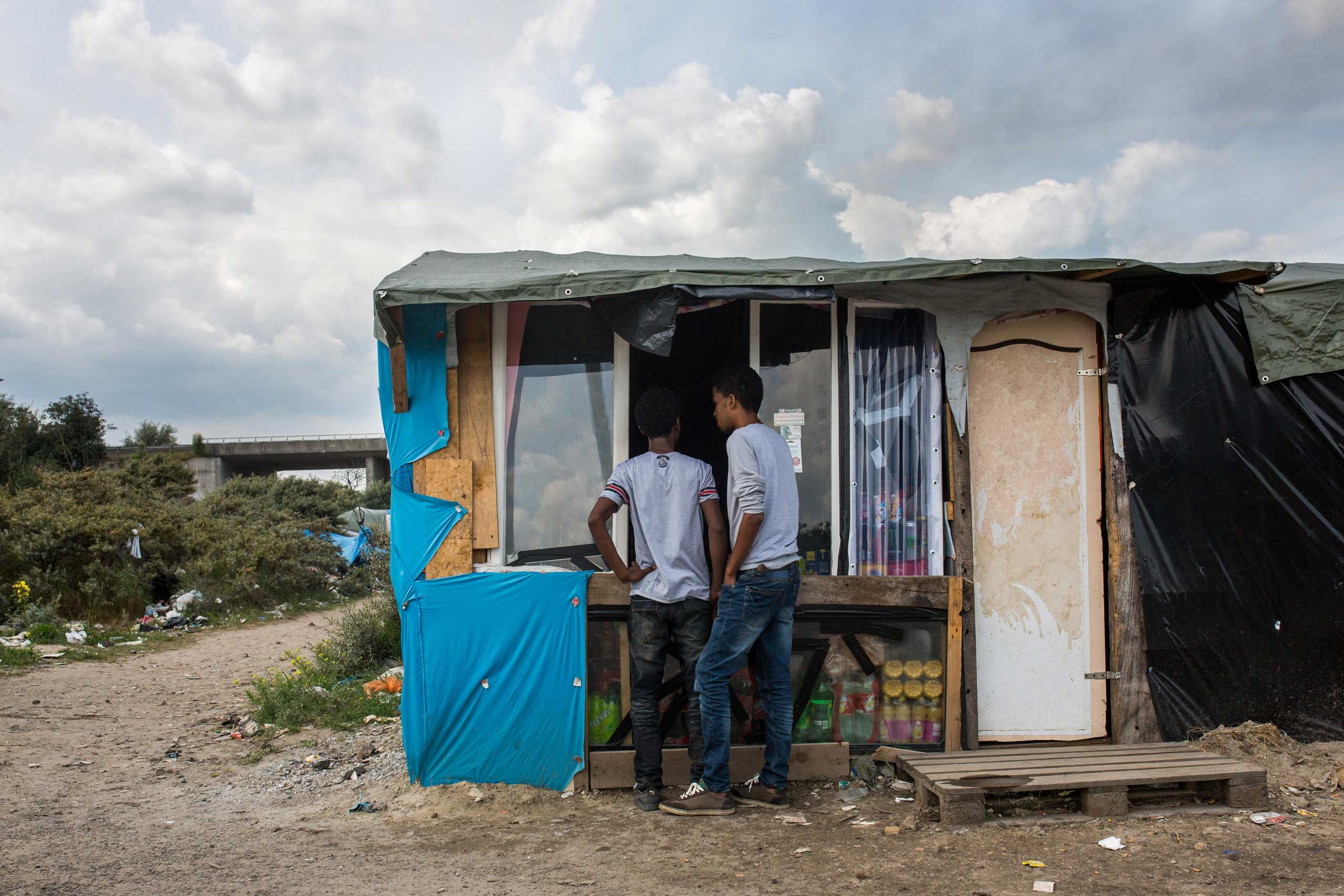Men buy from a shop run by Afghanis at a make shift camp near the port of Calais, on July 31, 2015.
