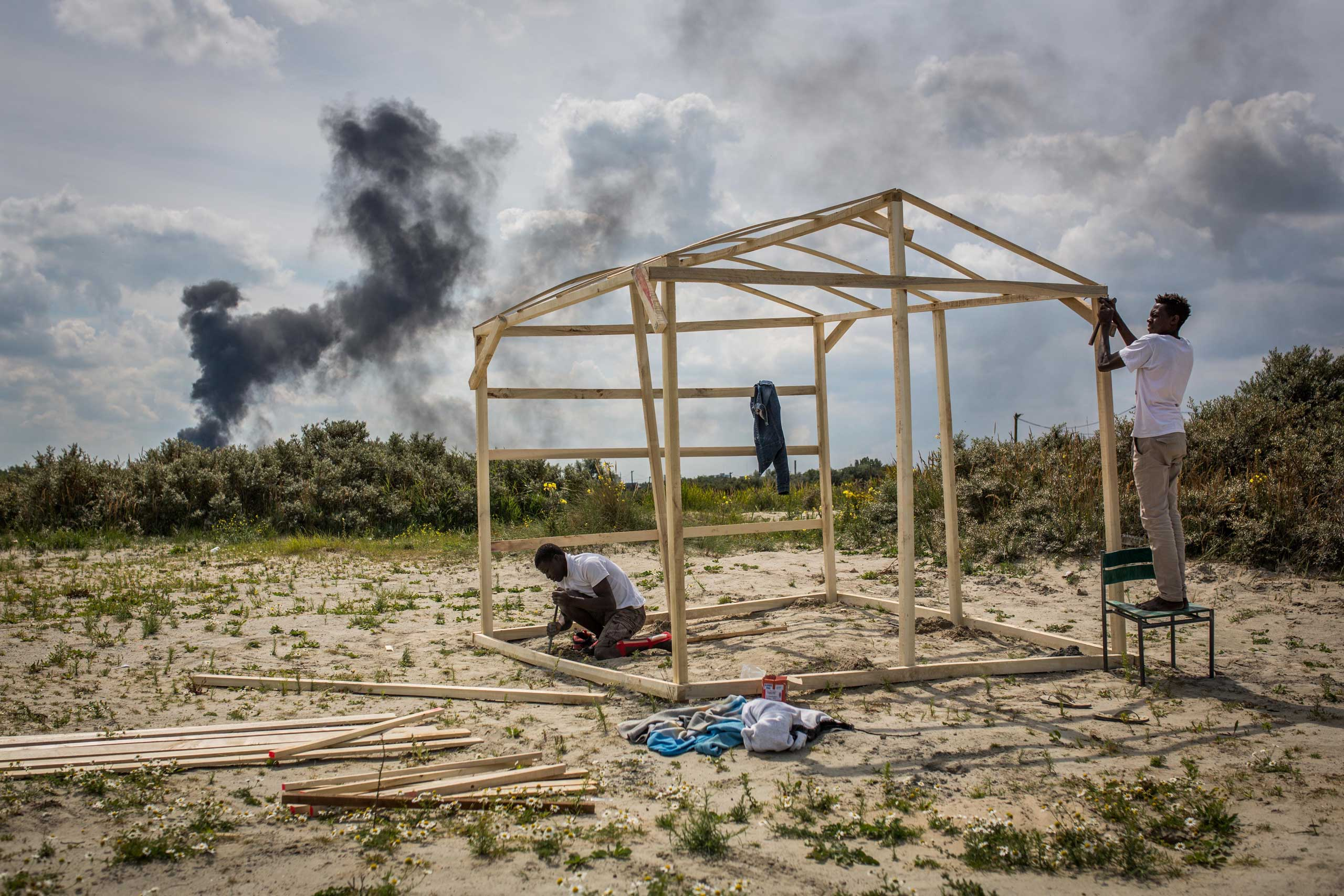 Gamal and Sabry from Sudan build a wooden structure at a make shift camp near the port of Calais, on July 31, 2015.
