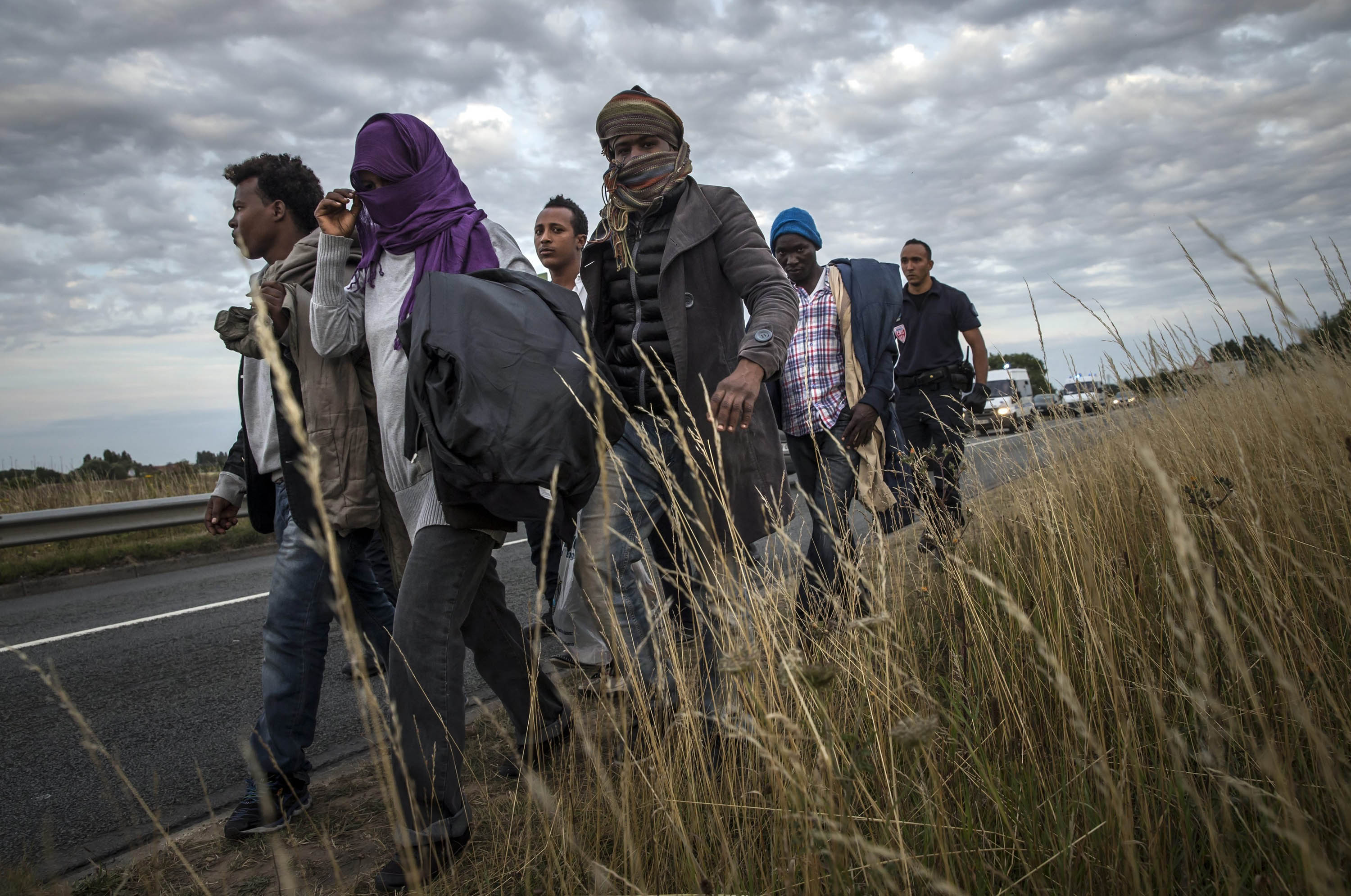 French police officers escort Eritrean migrants away from the Channel Tunnel entrance on Aug. 3.