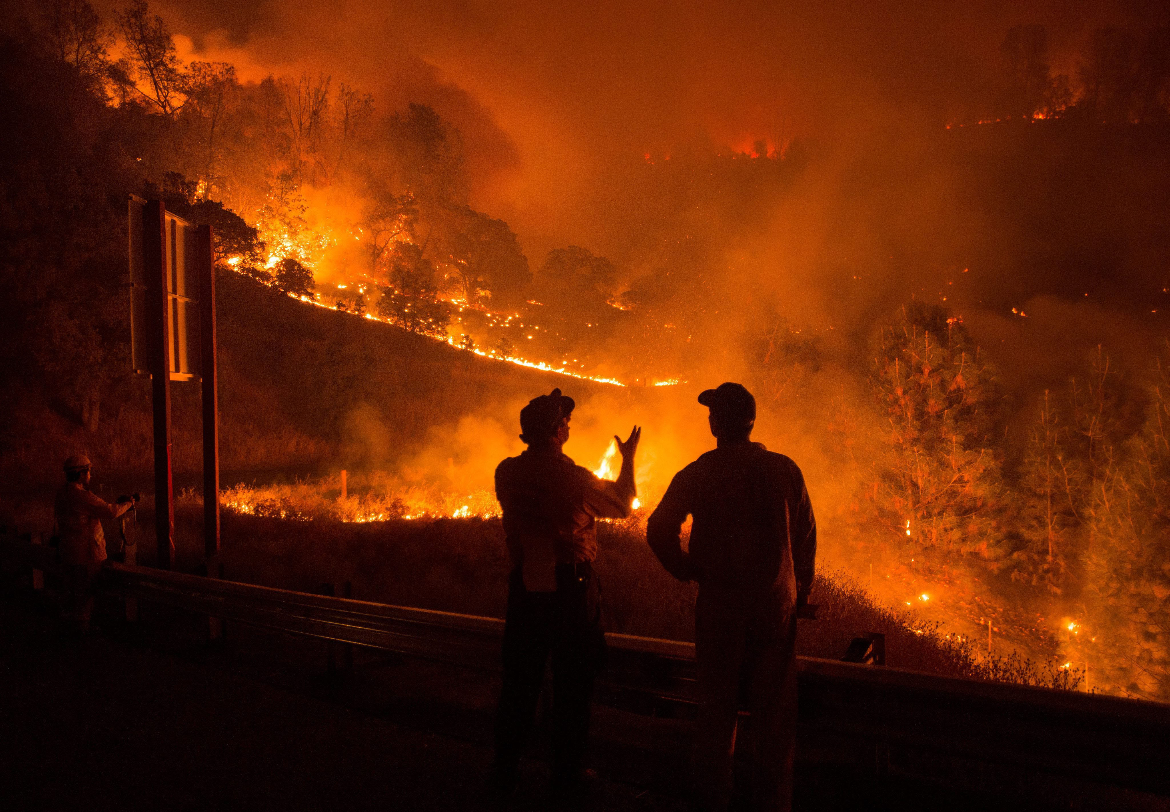 Firefighters Richard Dykhouse, left, and Dan McCabe confer as the Rocky fire burns near Clearlake, Calif. on Aug. 2, 2015.