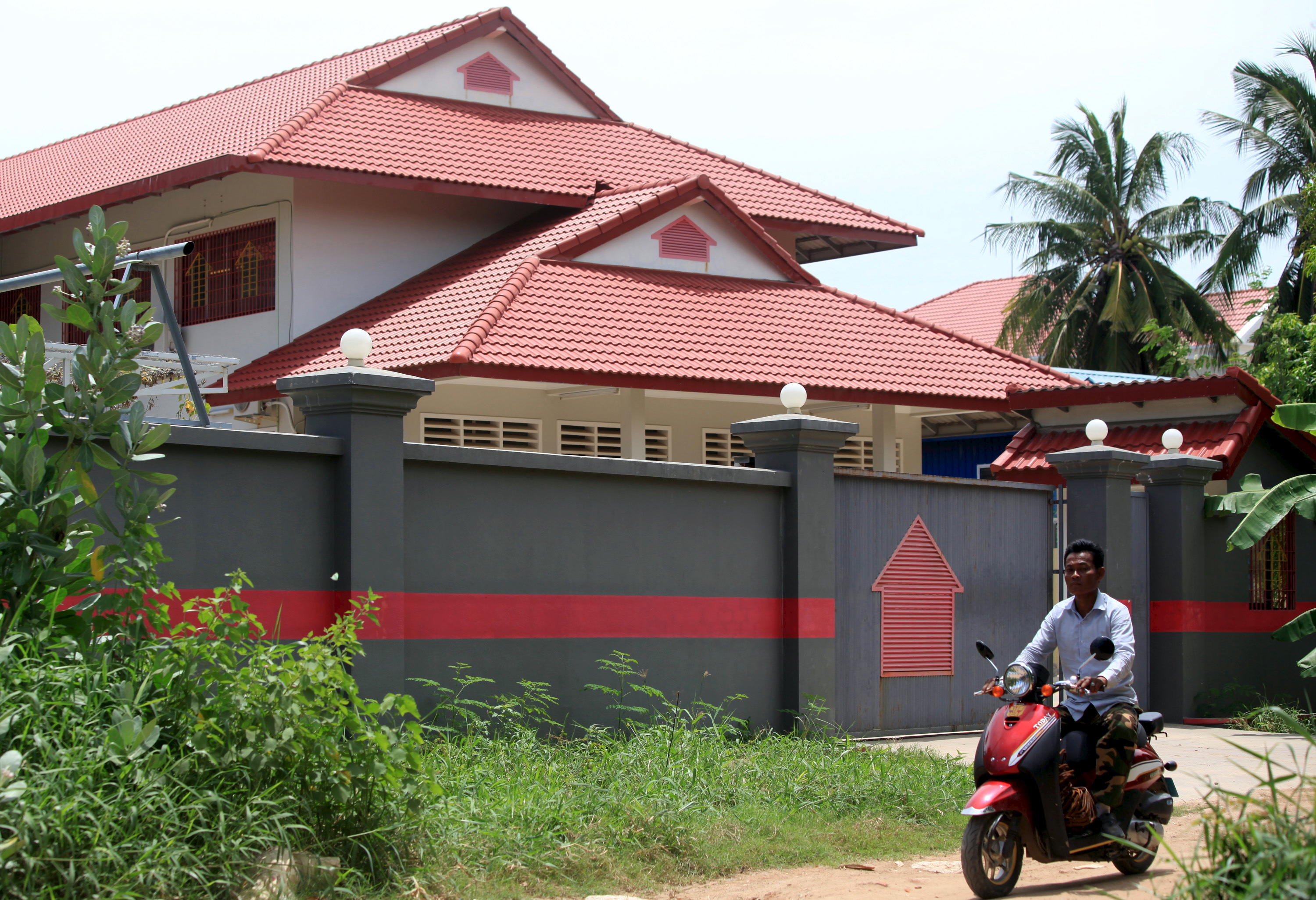 A man rides a motorcycle past a house that is used to temporarily house asylum seekers sent from a South Pacific detention centre, in Phnom Penh, Cambodia August 31, 2015.