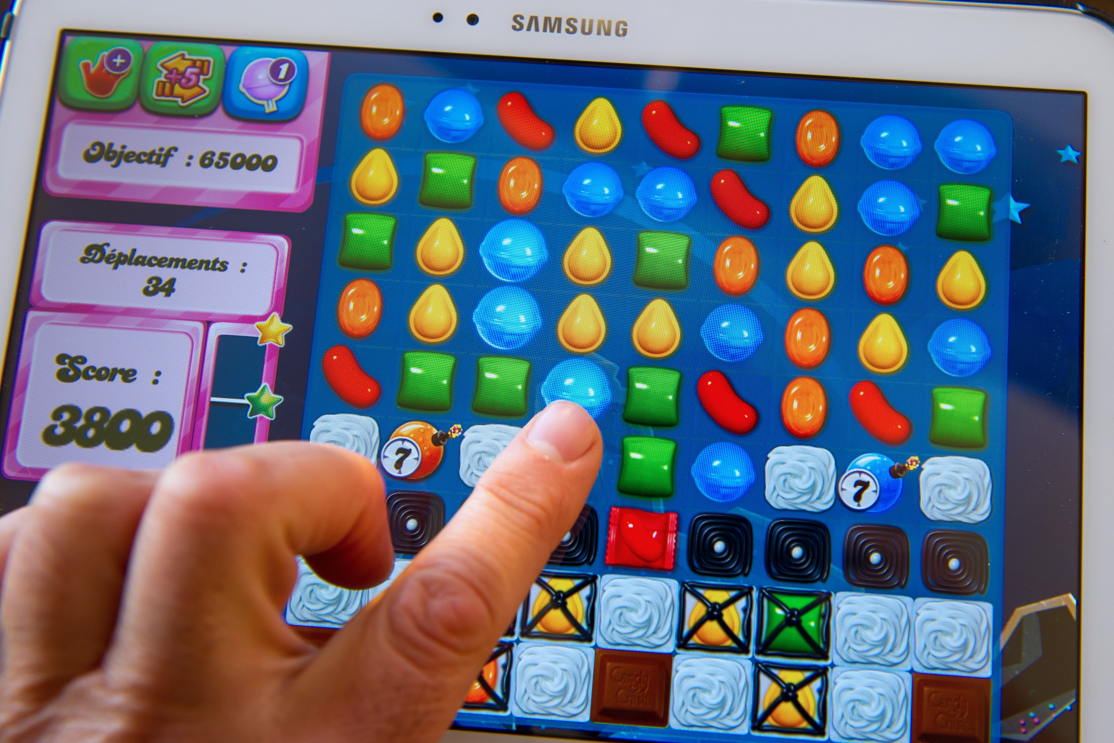A person plays Candy Crush Saga developed by British King Digital Entertainment, on March 6, 2014.