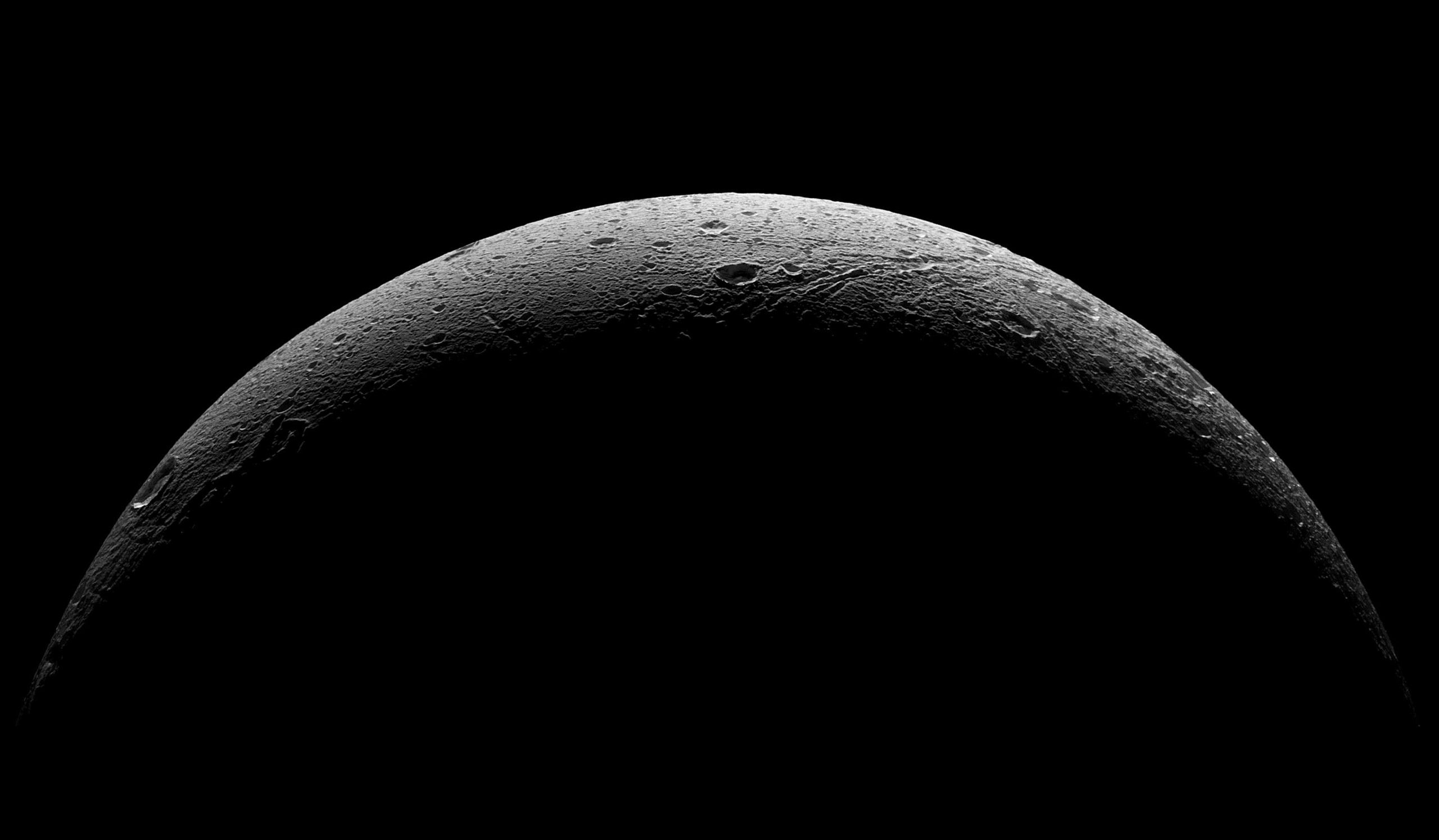 The rough and icy crescent of Saturn's moon Dione following the spacecraft's last close flyby of the moon on Aug. 17, 2015.