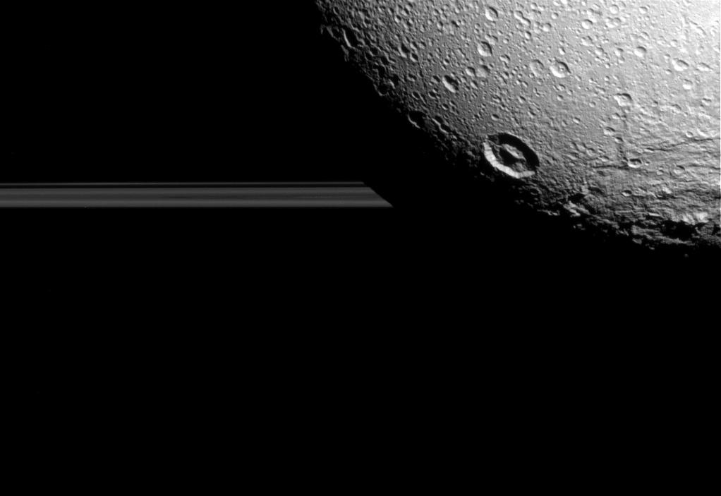 Saturn's moon Dione hangs in front of Saturn's rings.