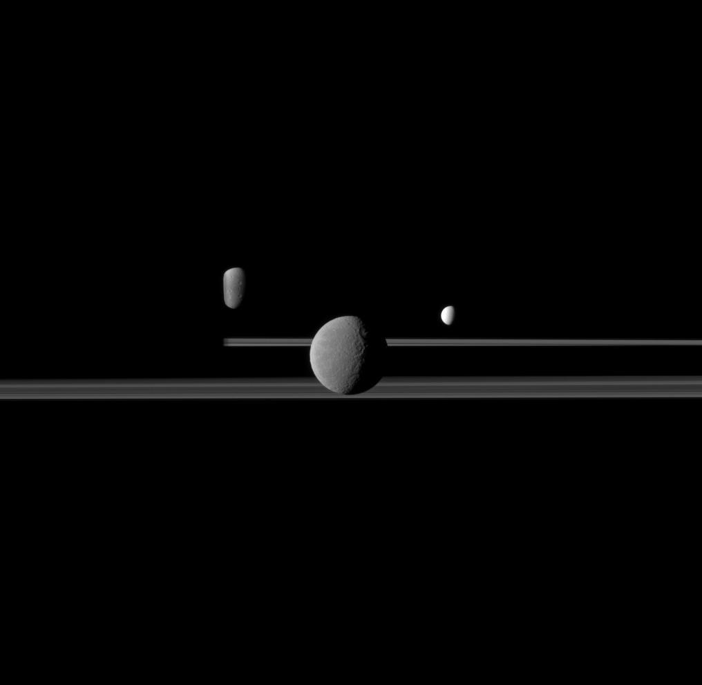 The Cassini spacecraft observed three of Saturn's moons set against the night side of the planet in this image from April 2011.