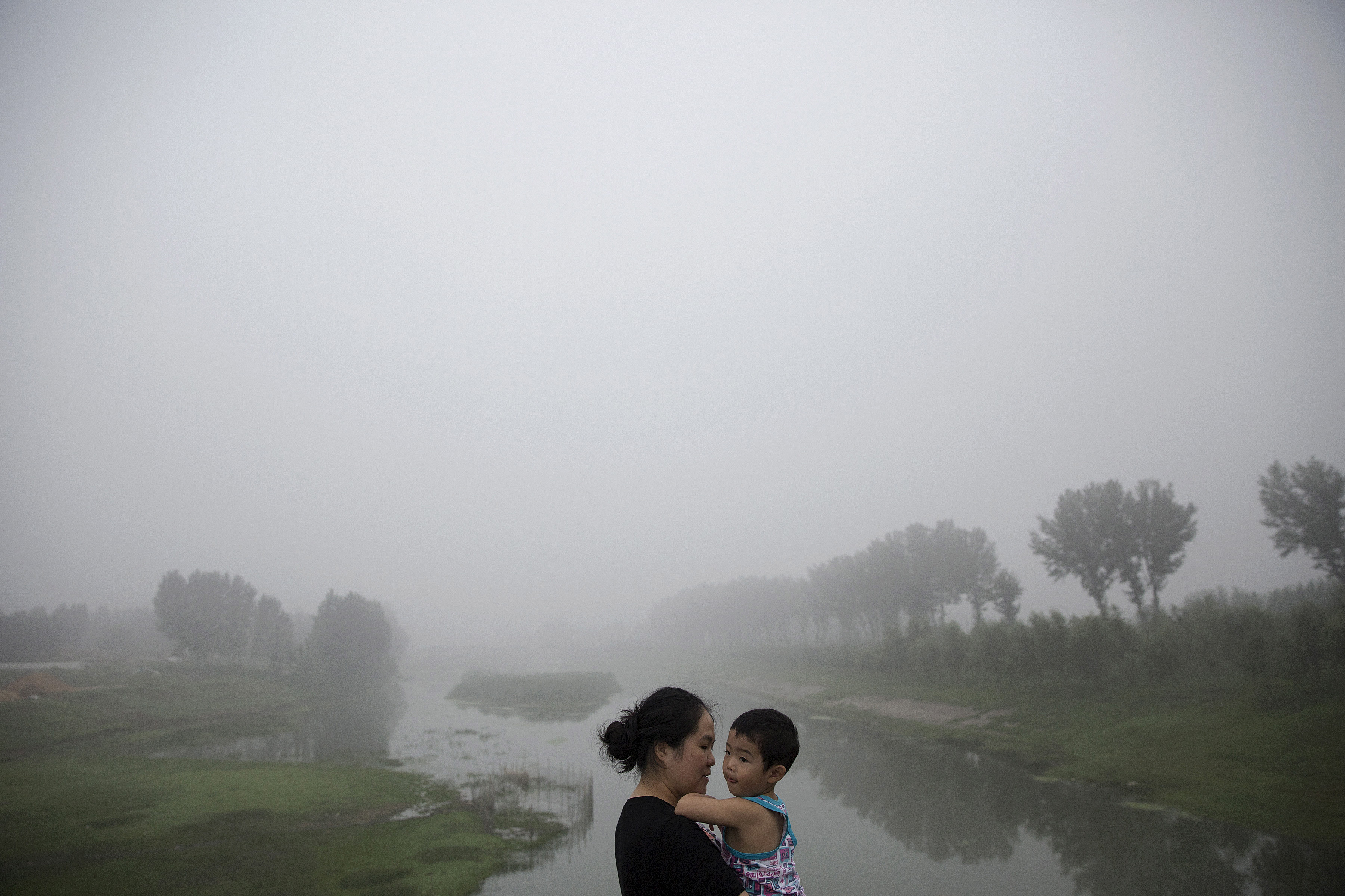 A woman holds a child as travelers wait for the highway from Beijing to China's Hebei Province to reopen after it was closed due to low visibility, on a heavily polluted morning on Aug. 3, 2015.